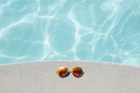 gold framed orange lens Aviator-style sunglasses beside pool