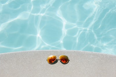 gold framed orange lens aviator-style sunglasses beside pool sunglass zoom background