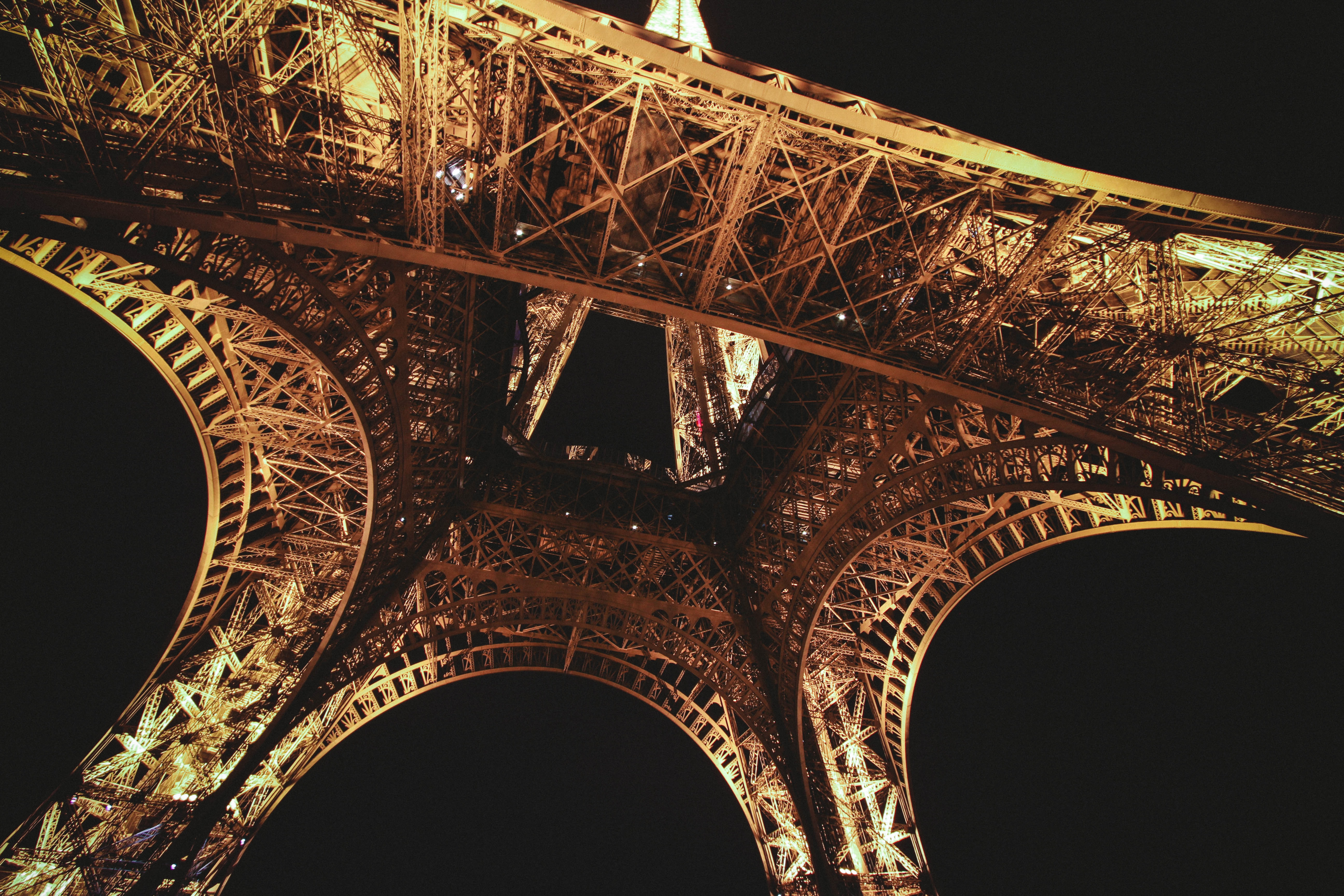 Looking up at the illuminated Eiffel Tower in Paris, France.