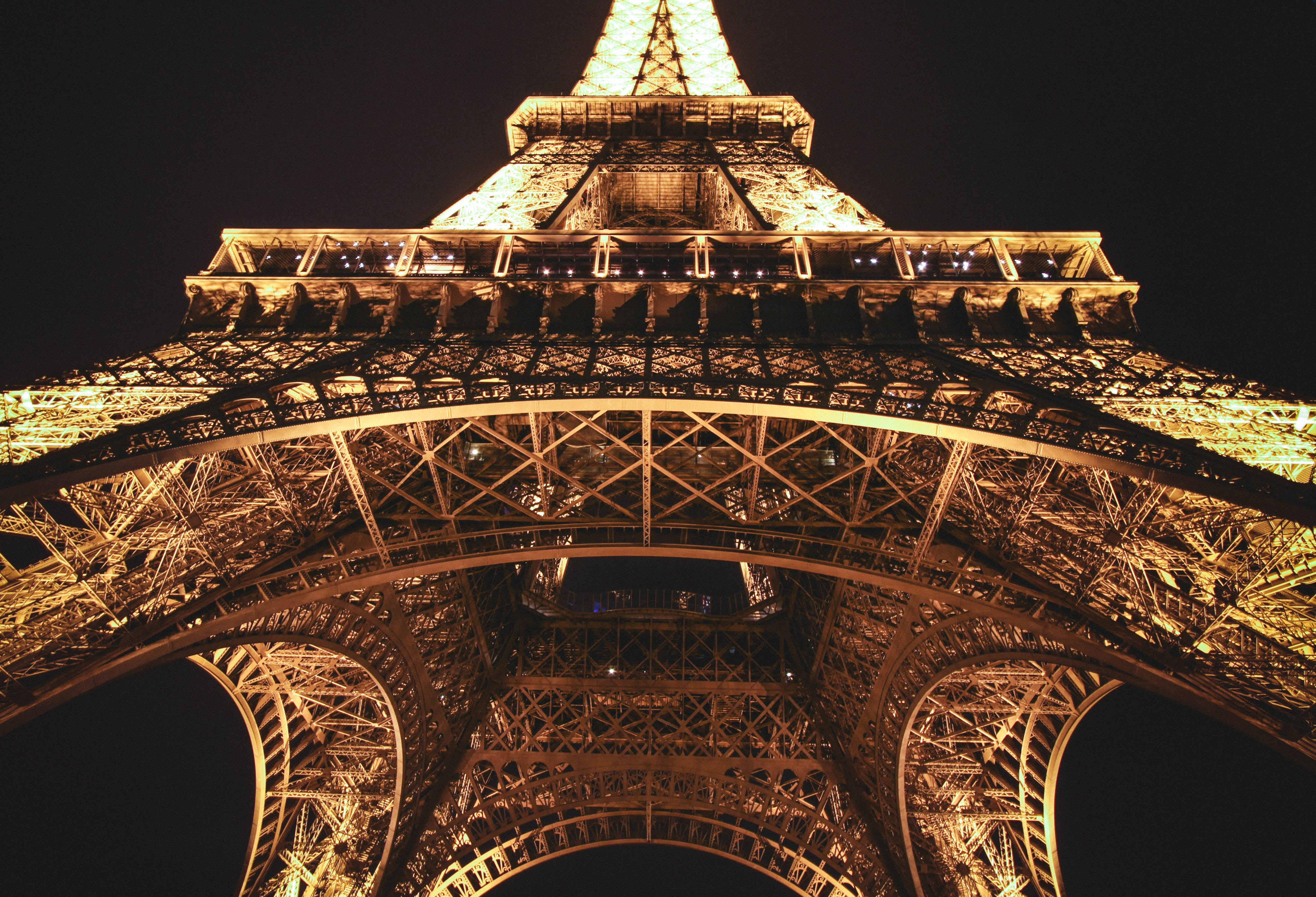 A centered shot looking up at the Eiffel Tower in Paris illuminated at night
