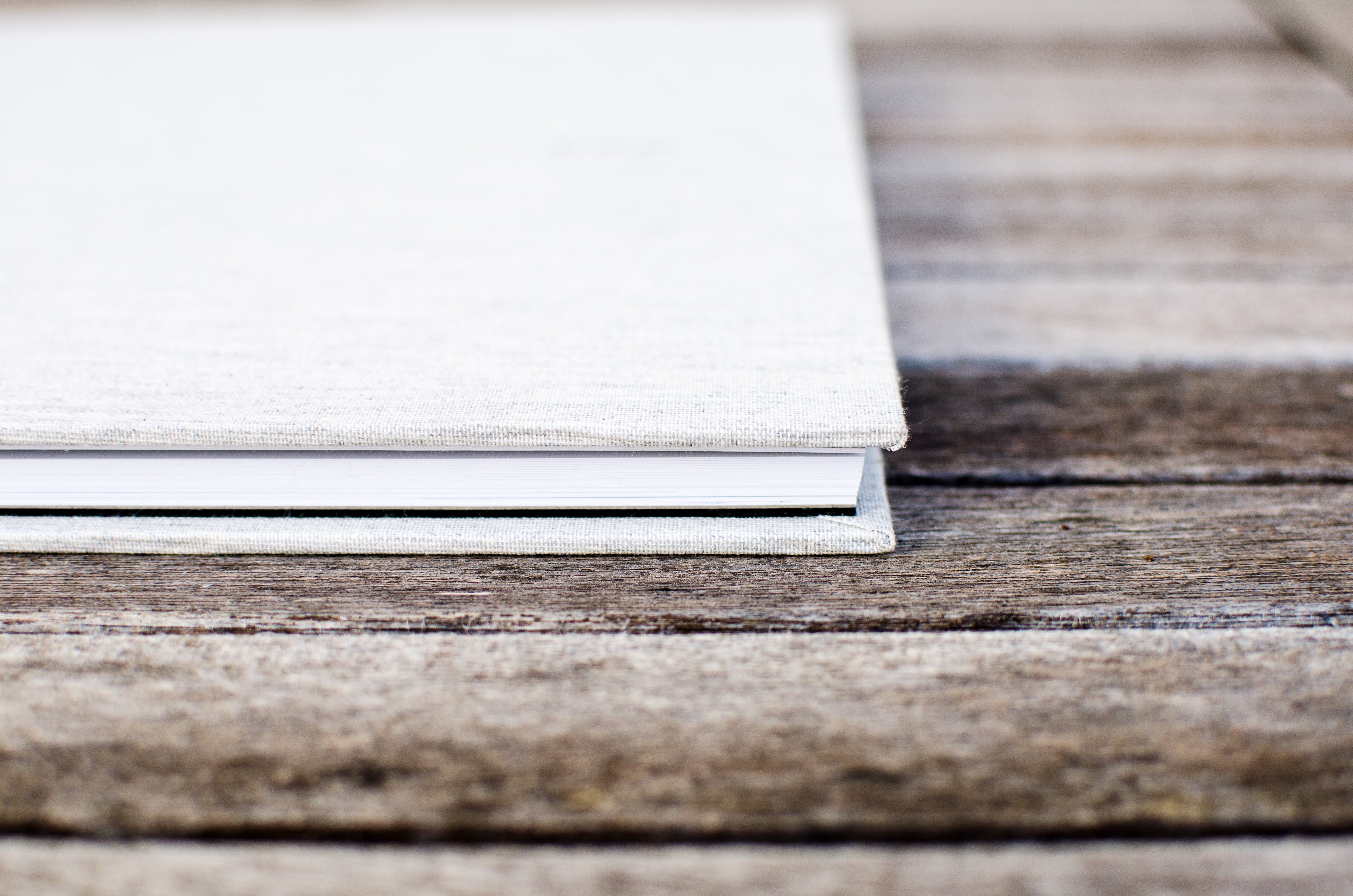 White hardcover book sitting on the wooden table
