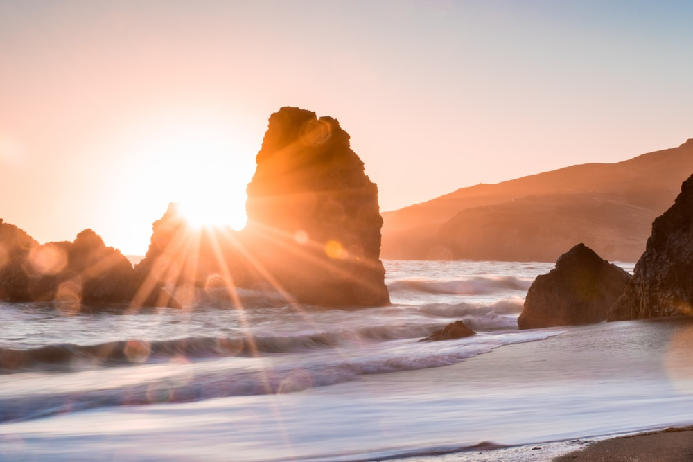 golden hour photography of rock formation on body of water
