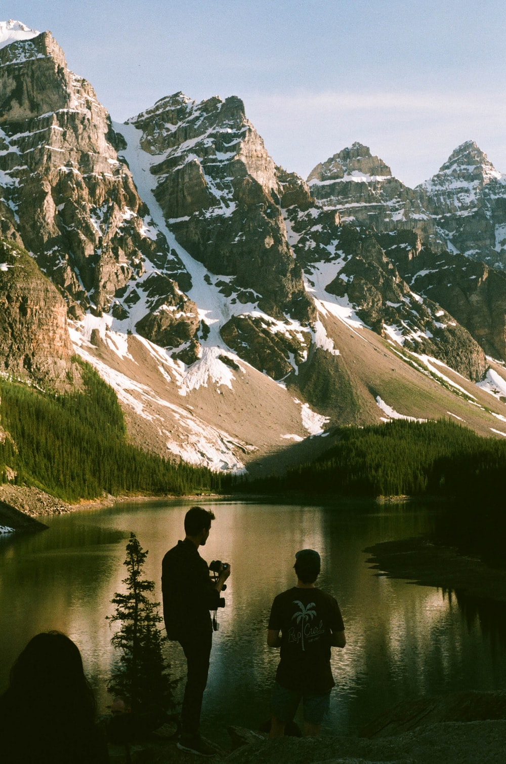 two men standing near body of water and mountain