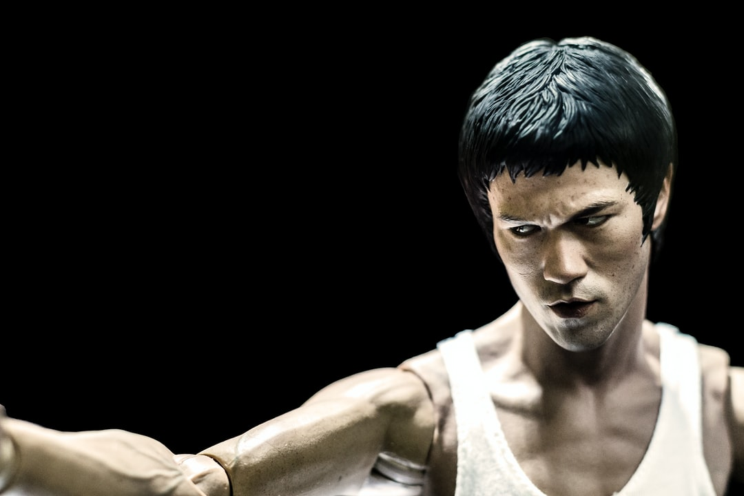 Bruce Lee figure in iconic martial art fight pose on black background