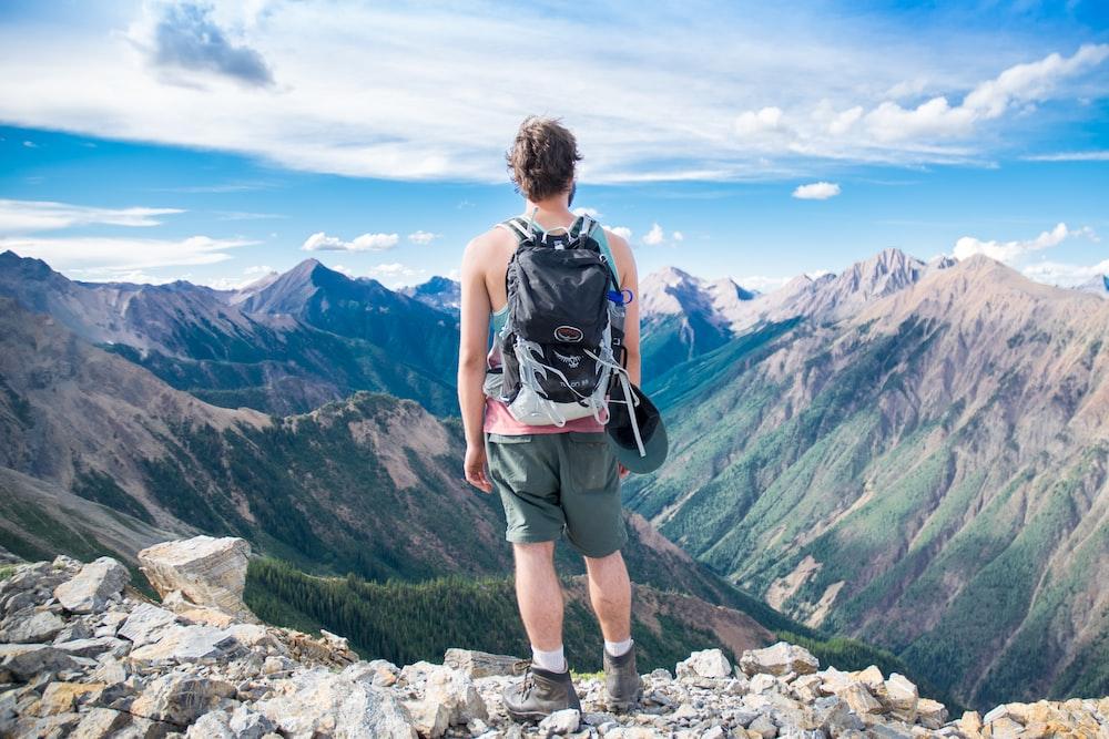 man standing on cliff facing mountain range
