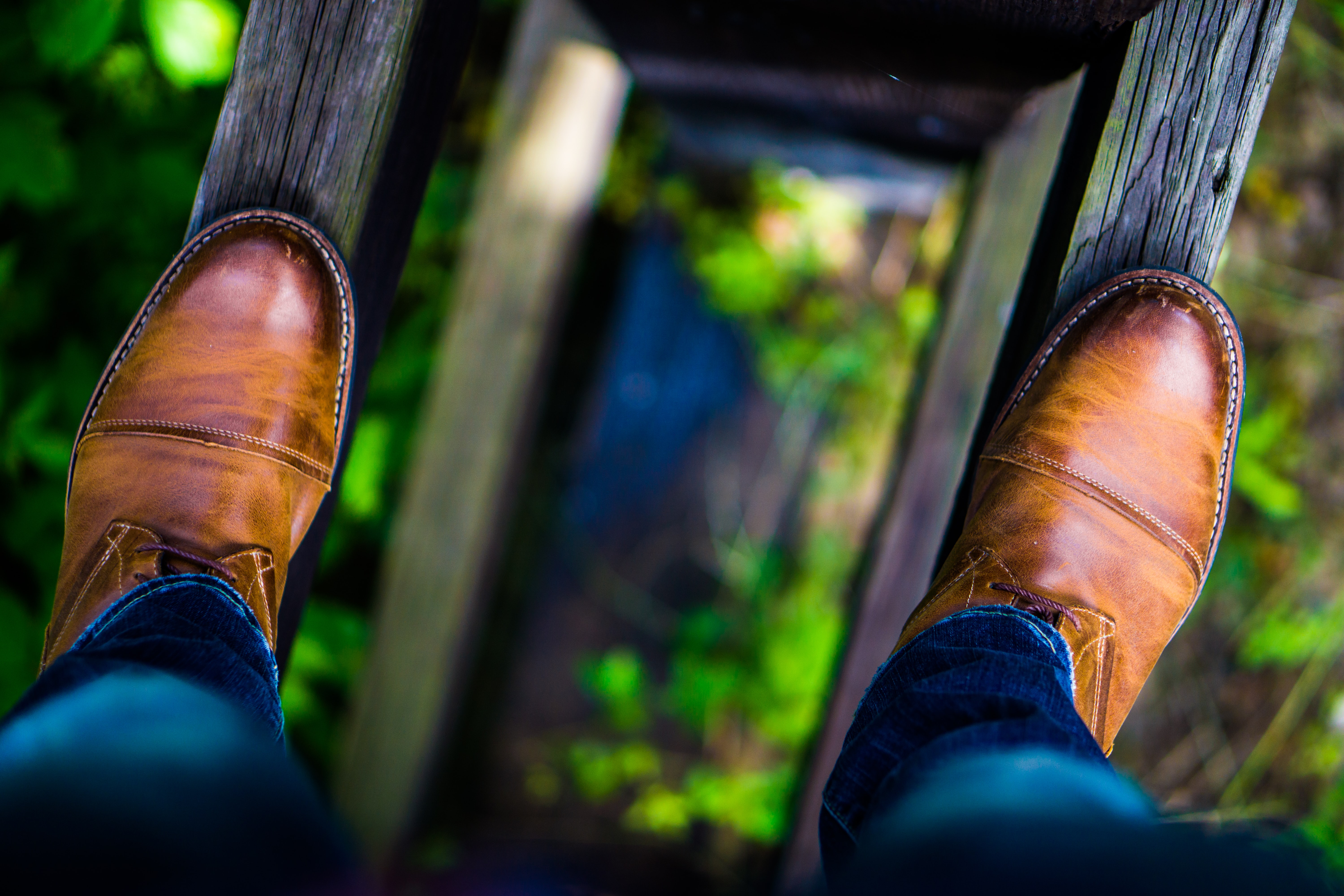 A man balancing on bridge exploring from above with leather shoes in Dublin