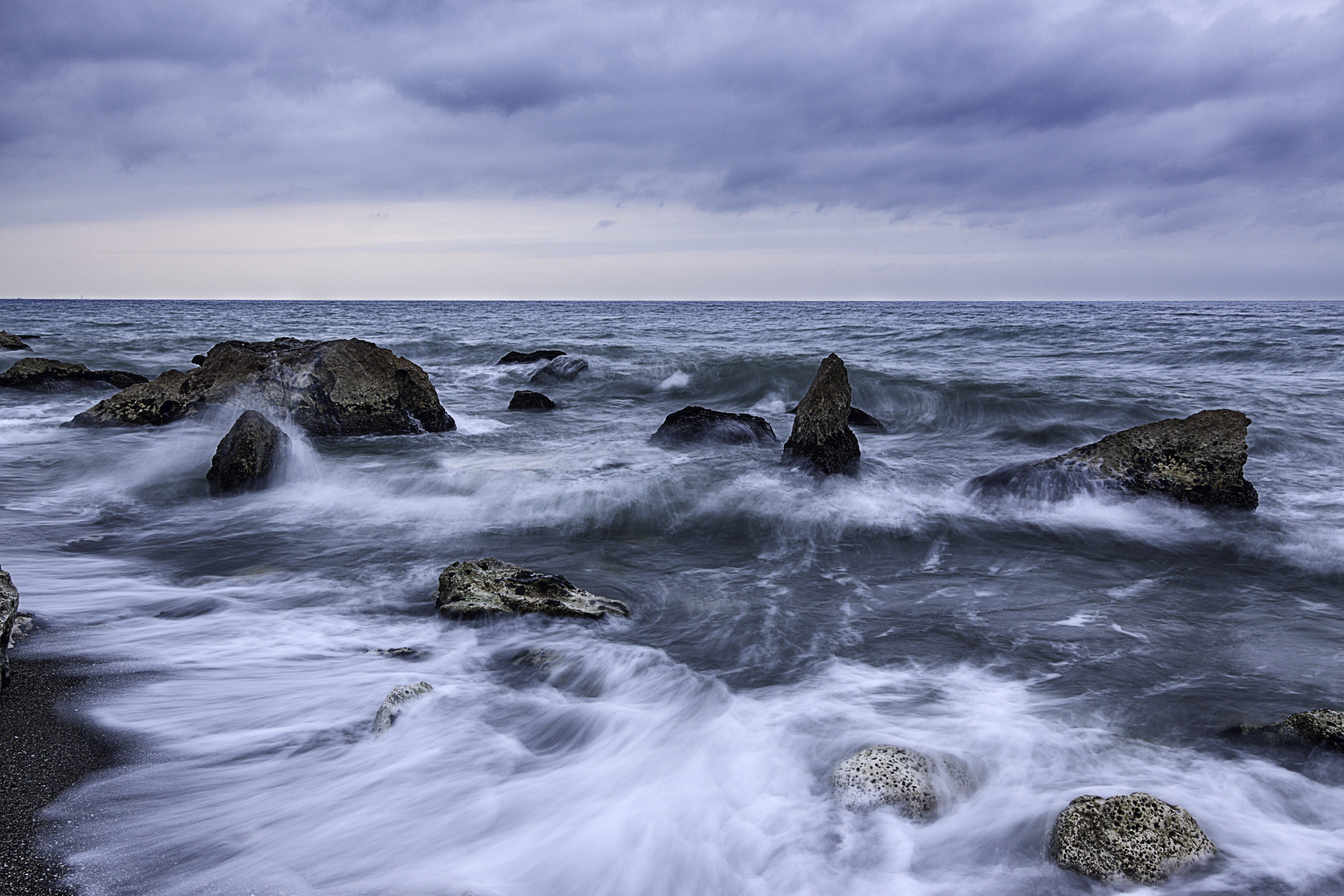 photo of a dancing waves with rocks