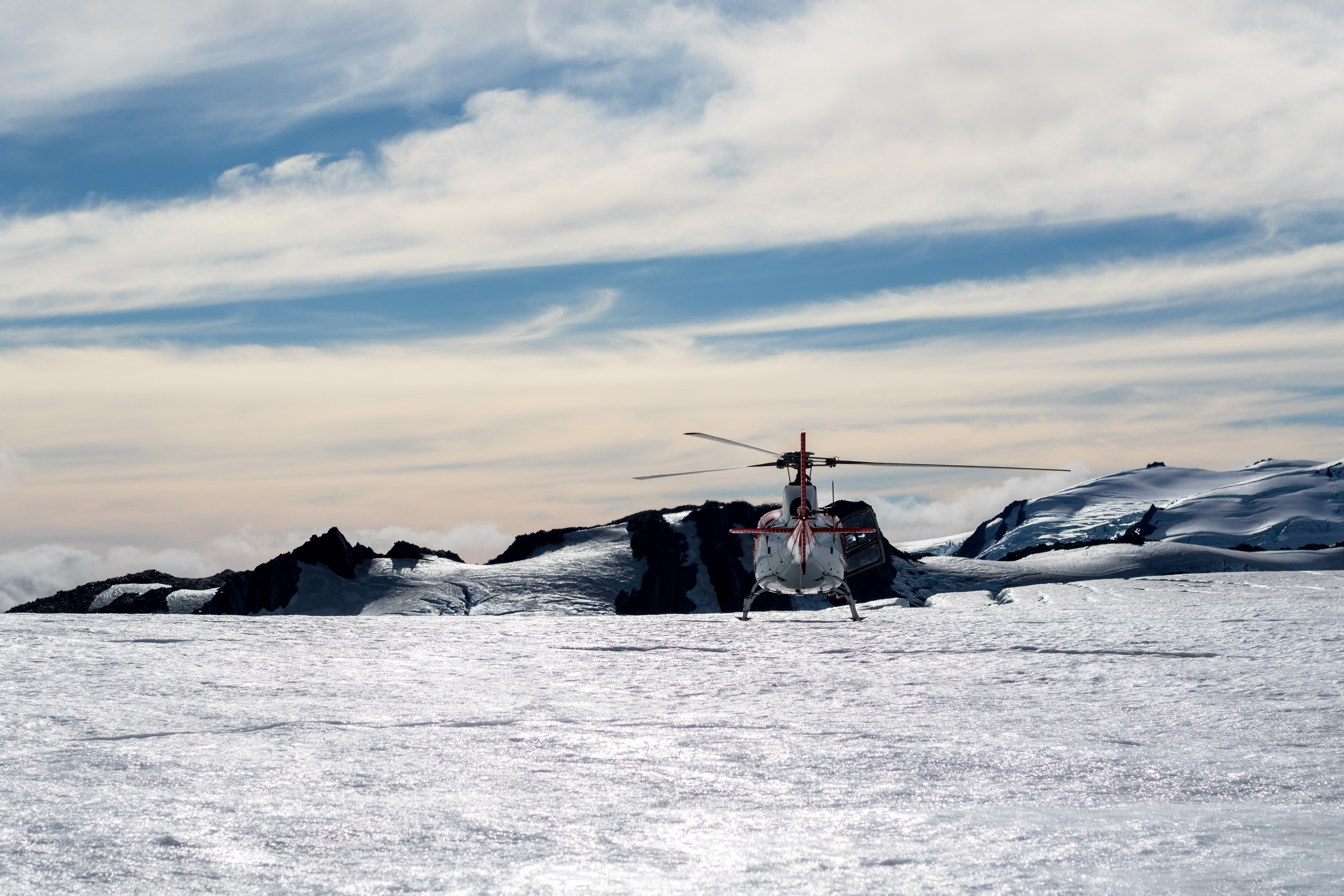 A helicopter sitting in a field of snow at Fox Glacier in New Zealand