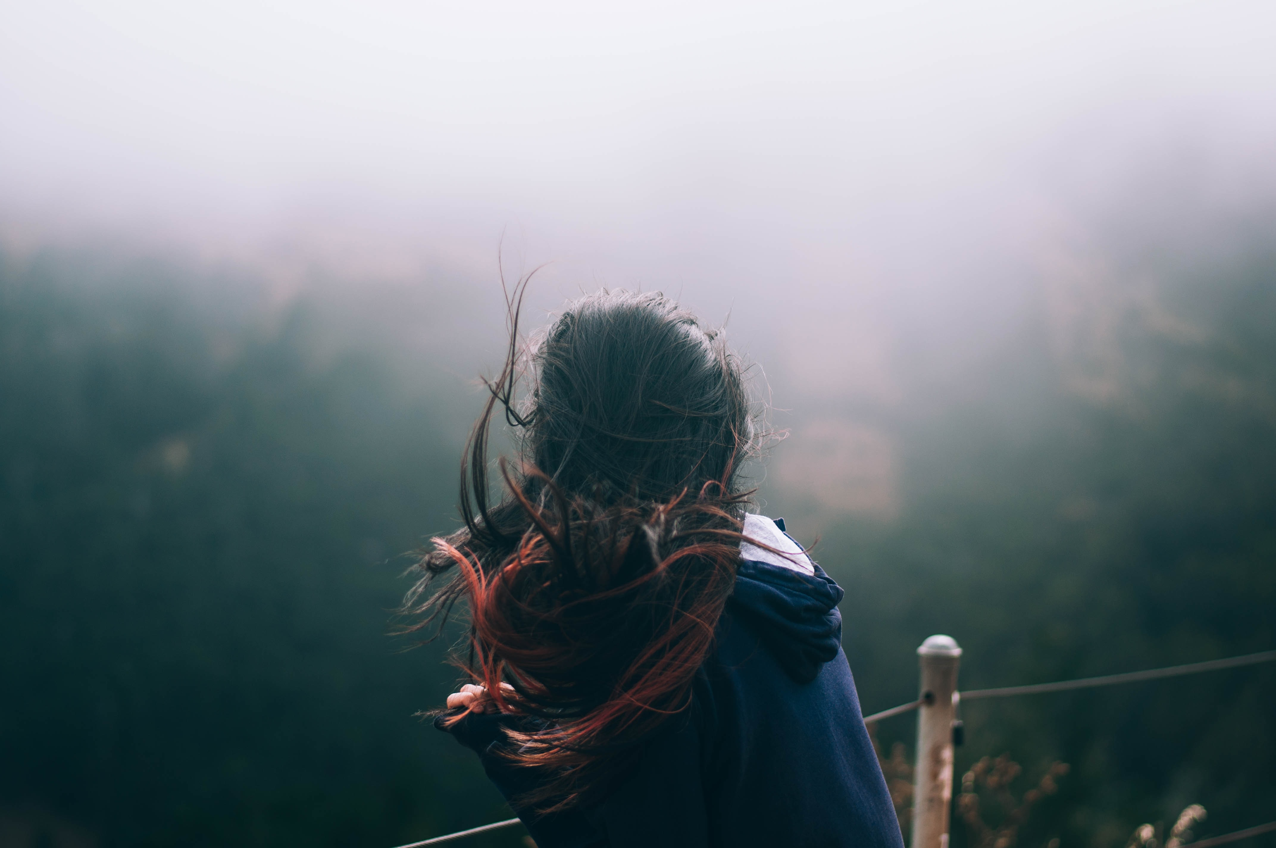 A girl's hair moving in the wind as she looks out at a fog covered San Francisco