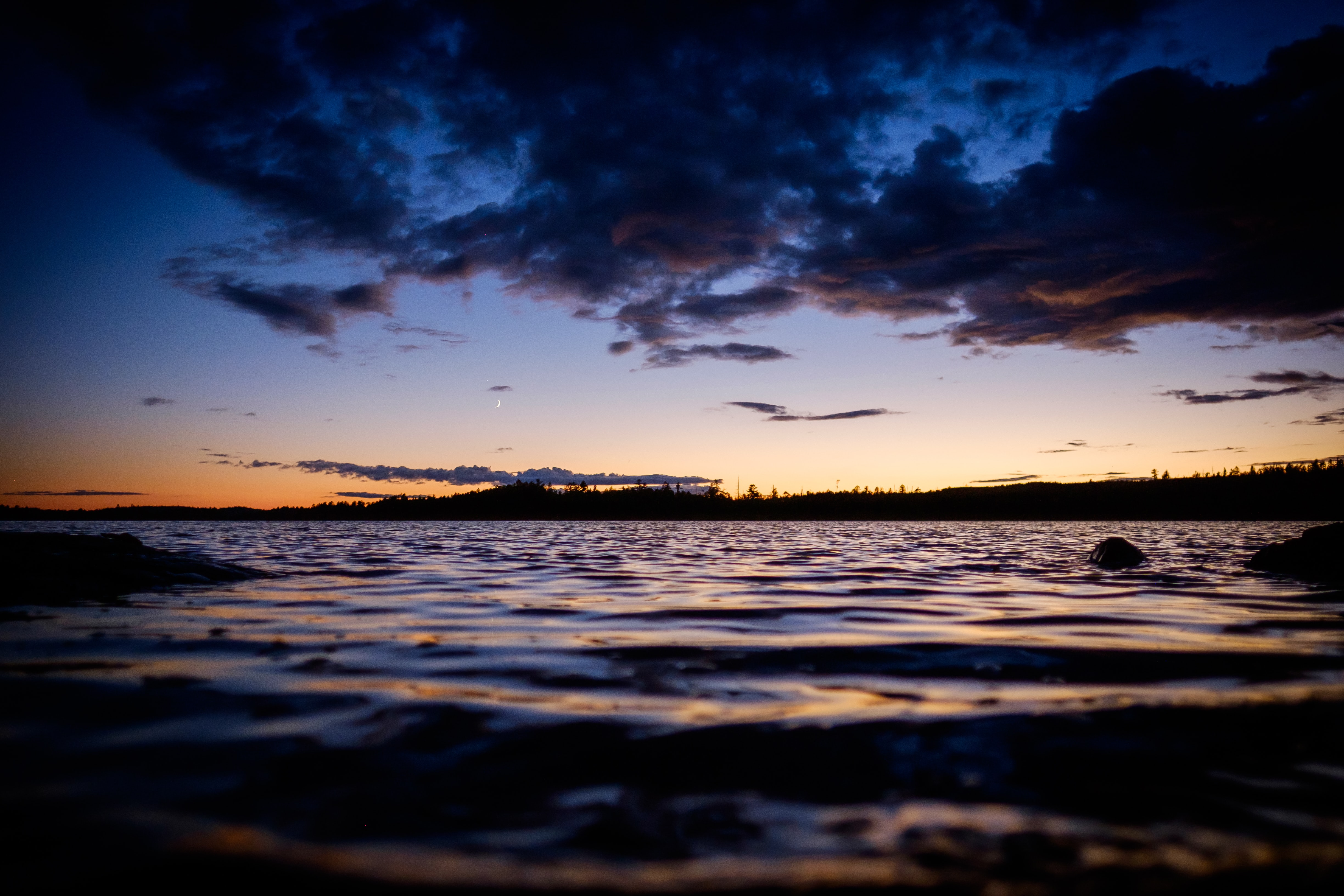 A dark sunset is reflected on the ocean ripples of Boundary Waters Canoe Area Wilderness
