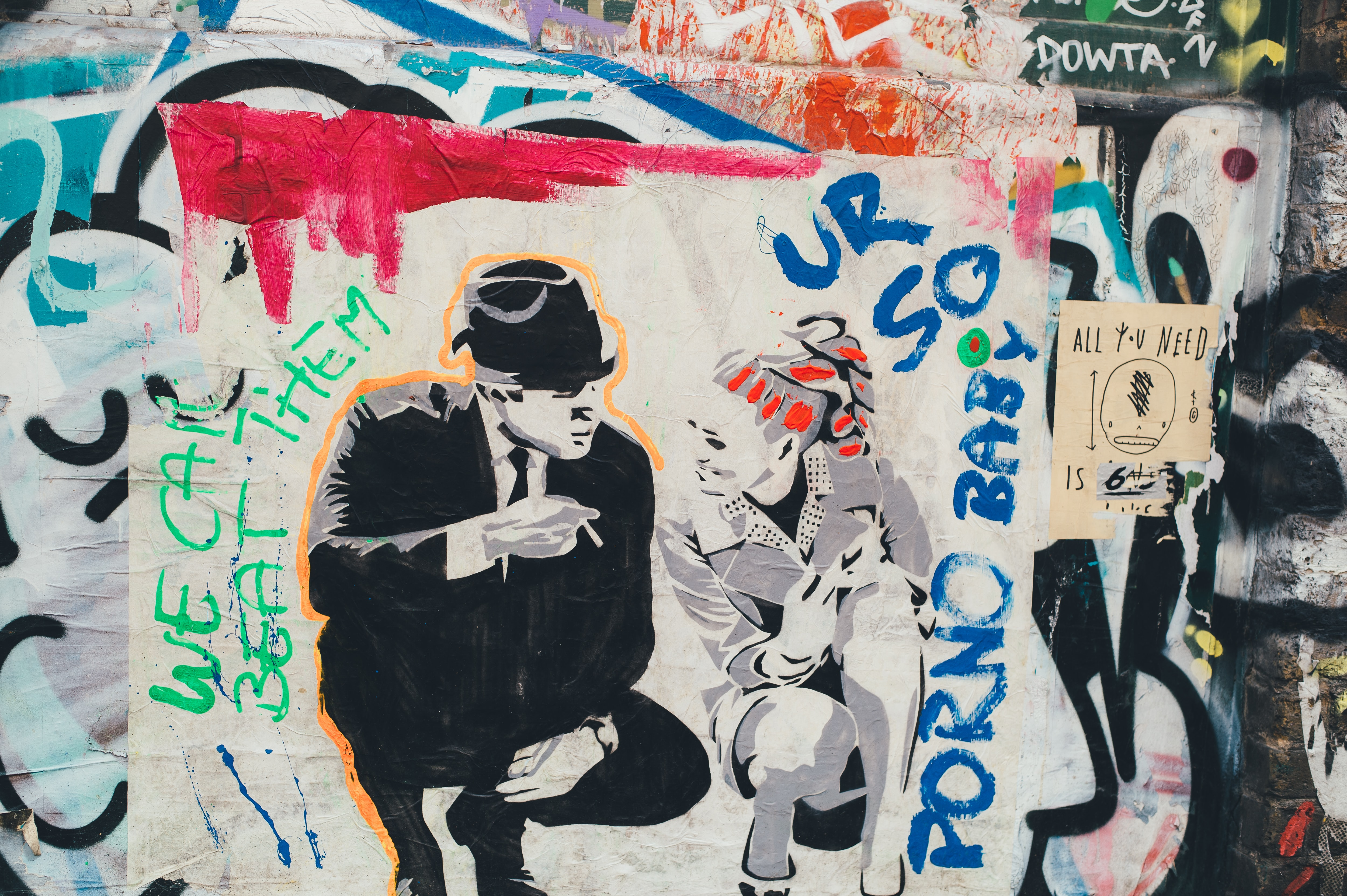 A graffiti graphic of a man in a suit with a top hat crouching while talking to a lady.