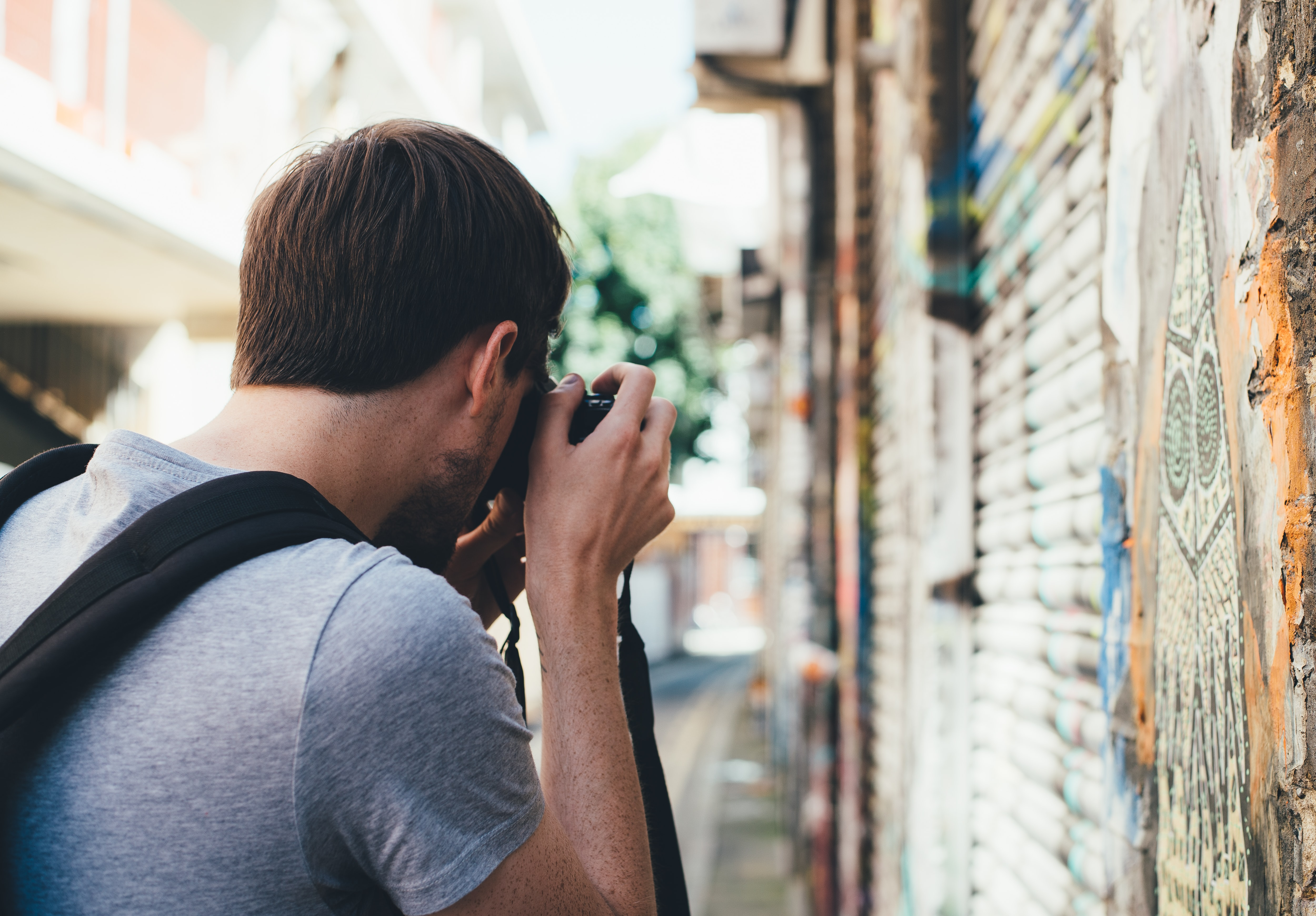 Man in Shoreditch wearing gray shirt and black backpack takes photo of graffiti street art on bright day