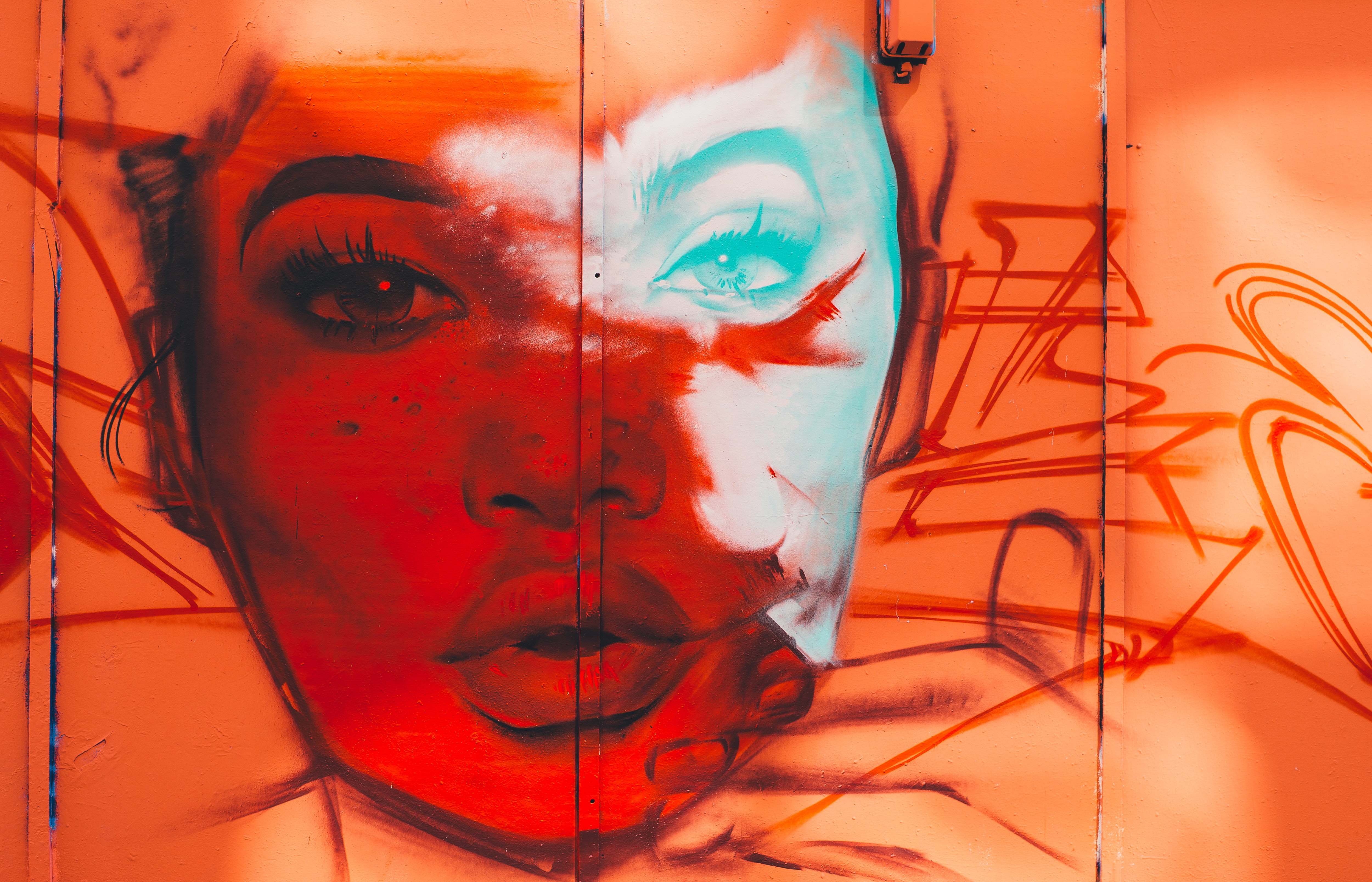 An intriguing red face graffiti painting on a wall.