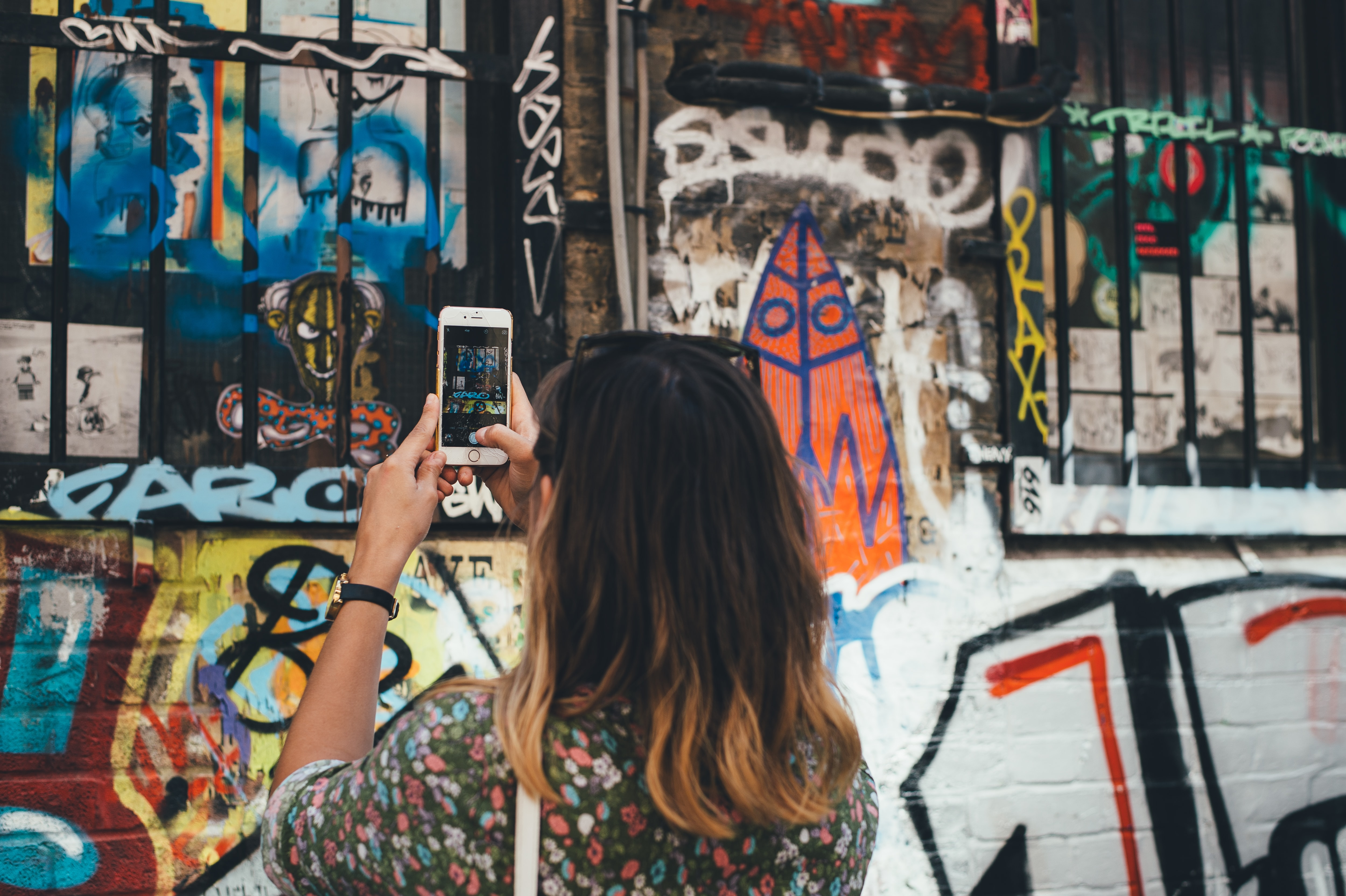 Woman in Shoreditch taking picture of graffiti art on brick wall with iron windows