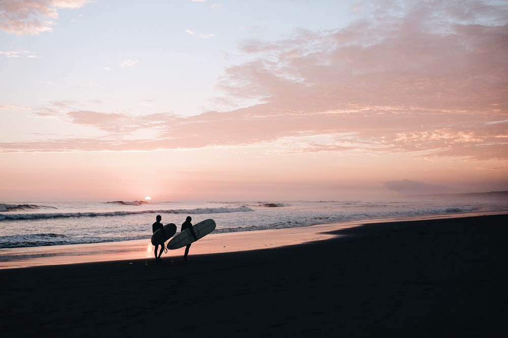 Silhouettes of two people carrying their surfboards on an empty beach during sunset