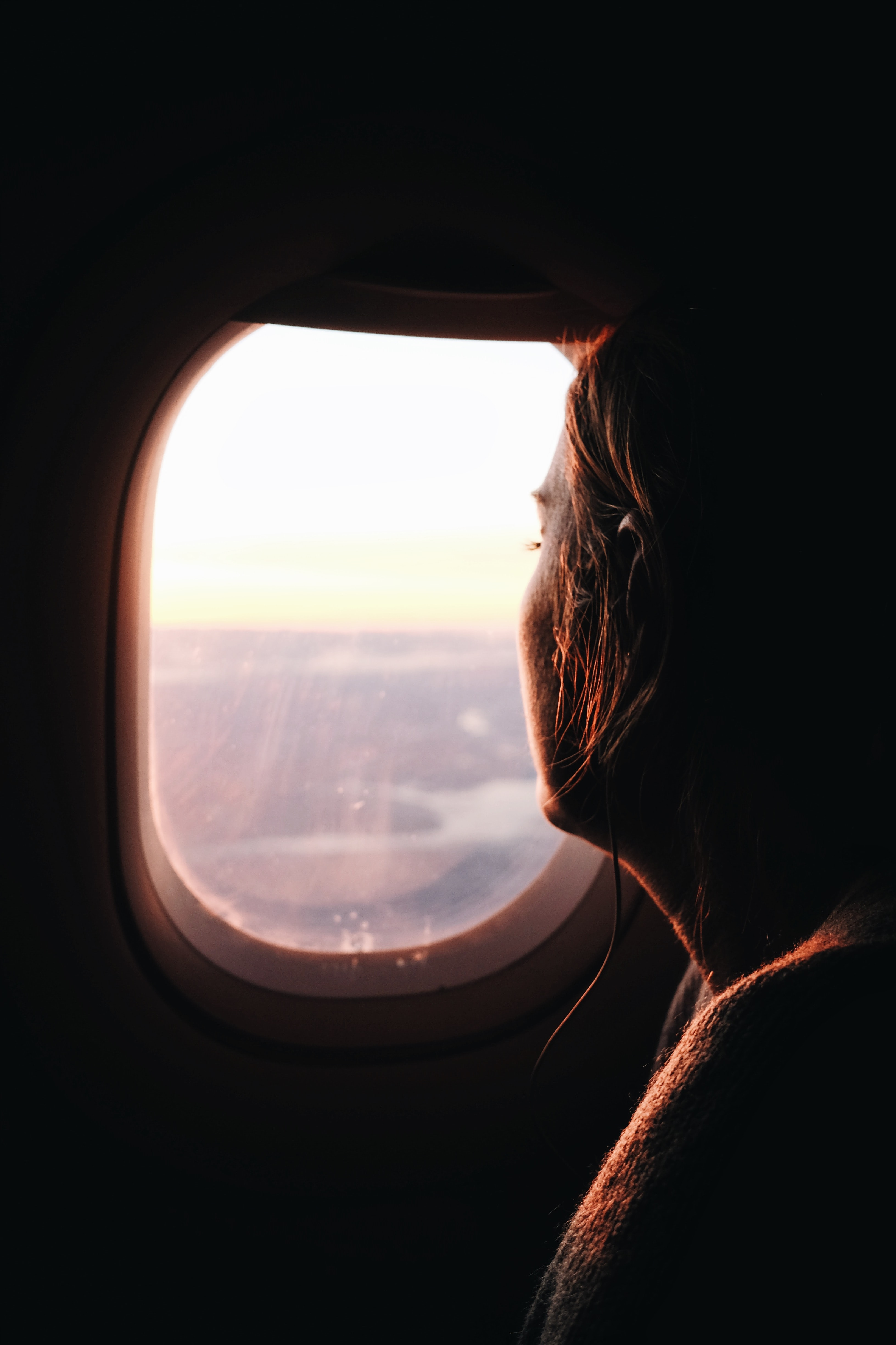 Woman with short hair peering from out of airplane window to sunset over São Paulo