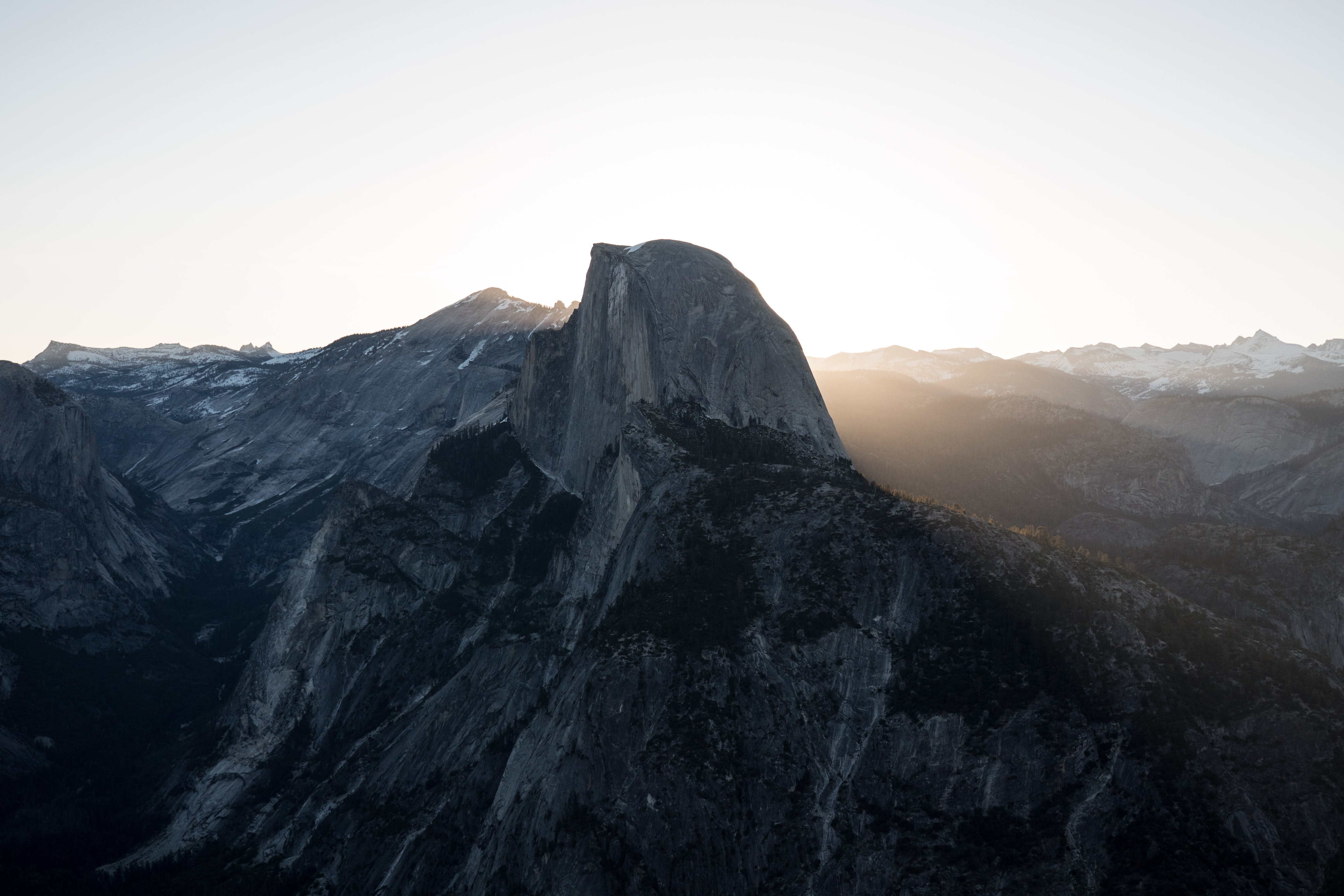A rocky peak in a mountain range illuminated by the rays of the sunset