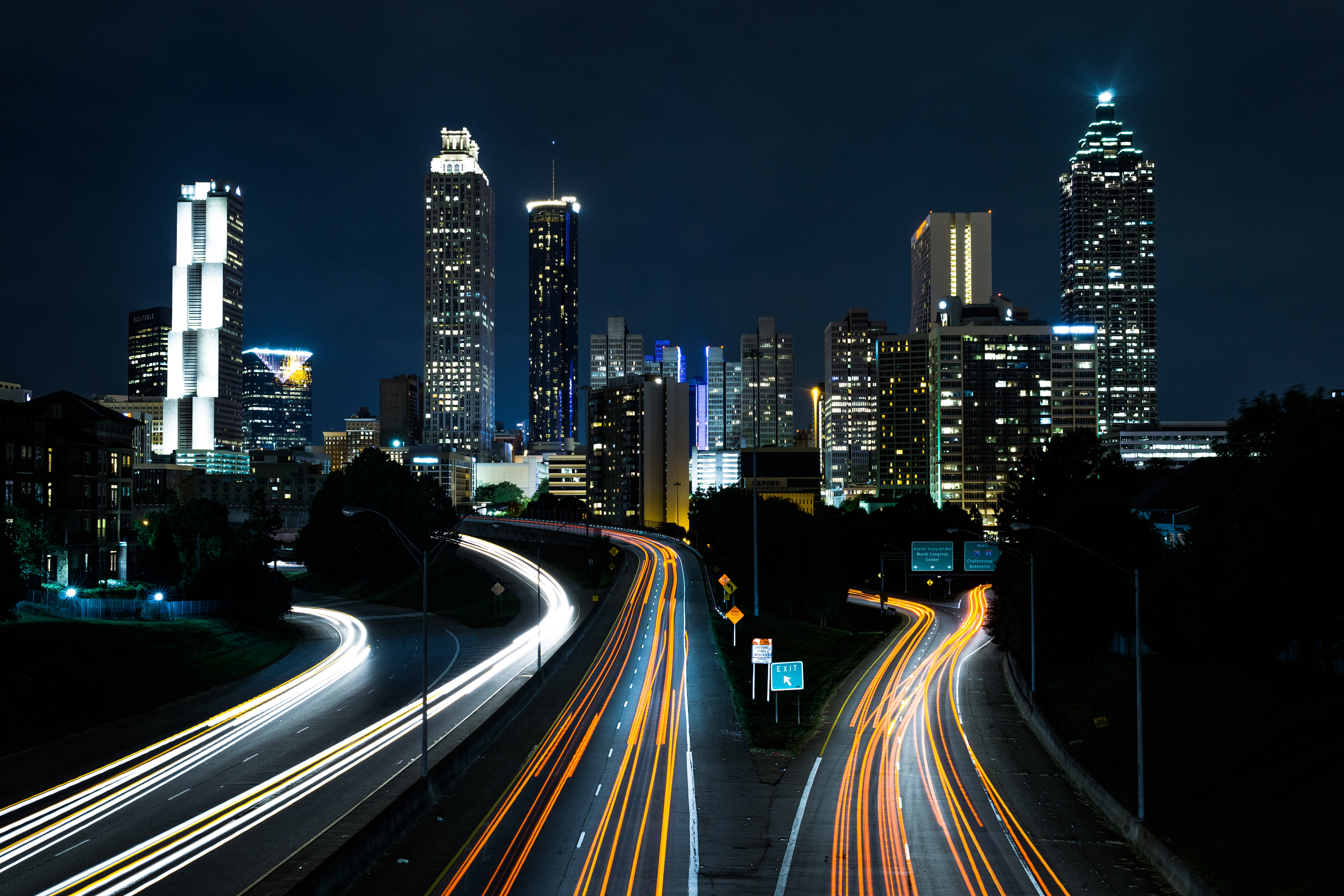A night-time shot of traffic light trails on the Jackson Street Bridge with the cityscape in the background