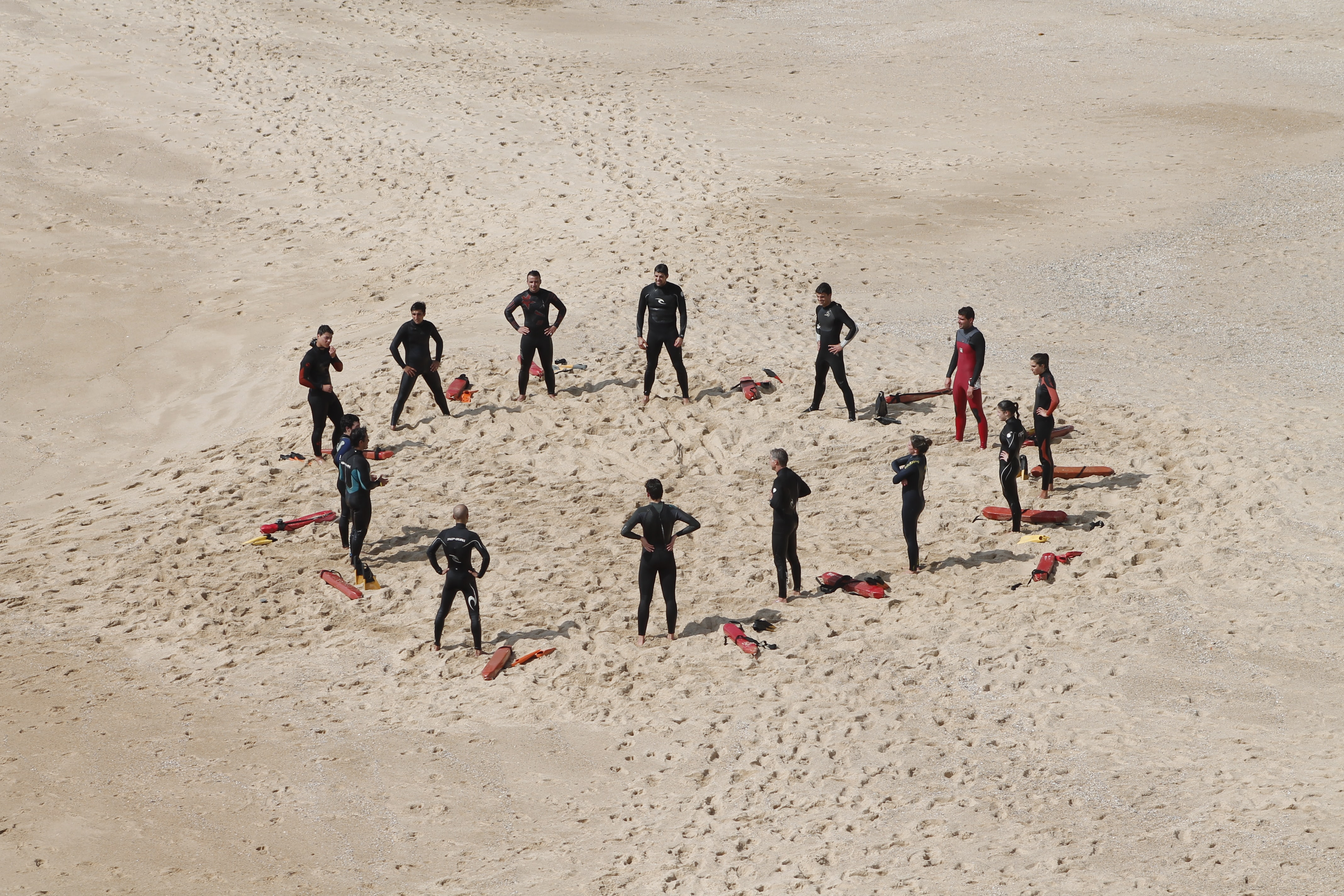 A circle of lifeguards in wetsuits doing a training course on a sandy beach