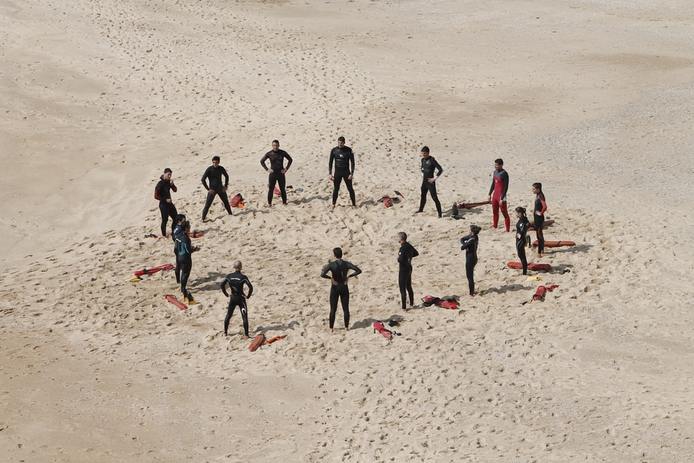 people standing forming a circle during daytime