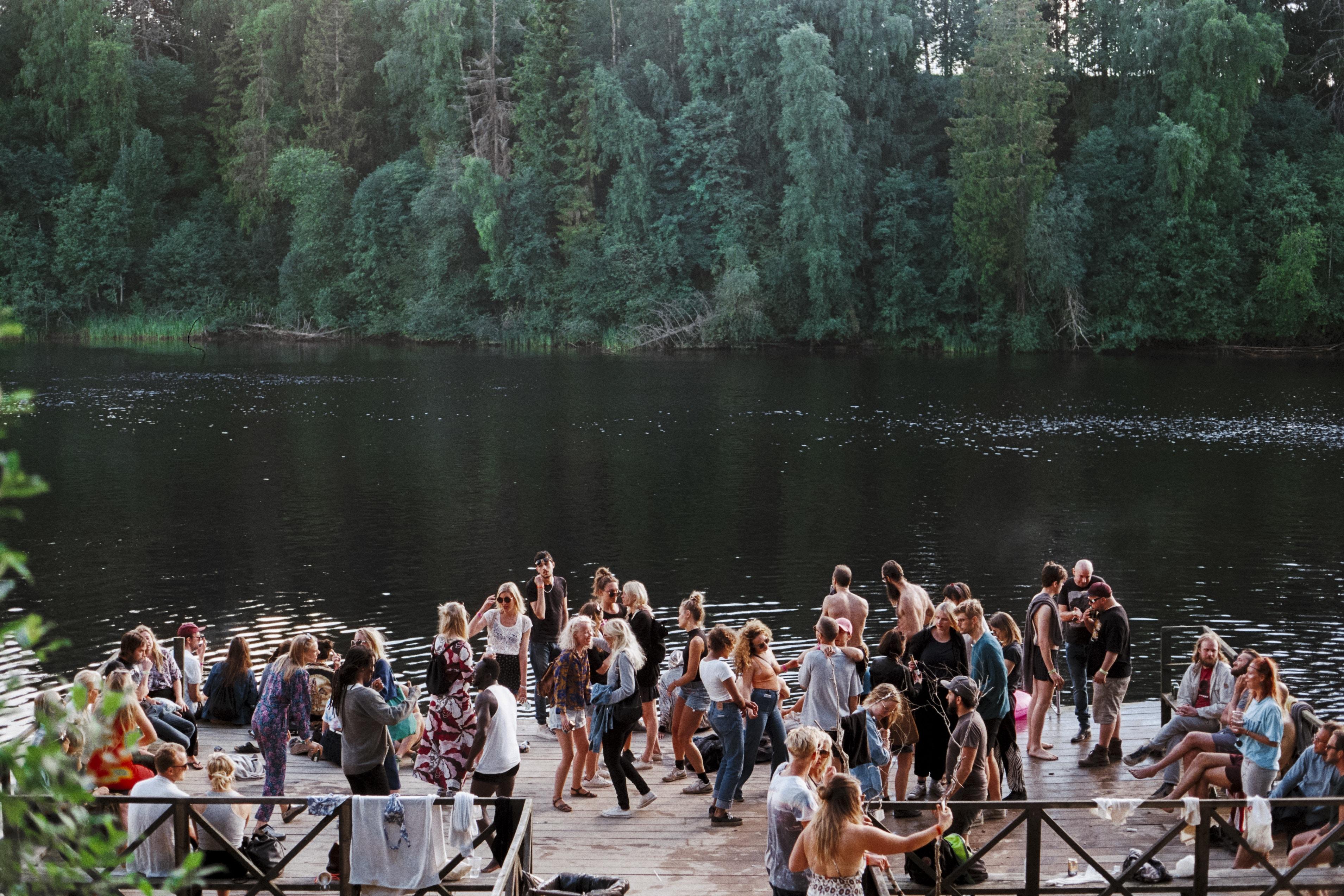 people standing beside lake