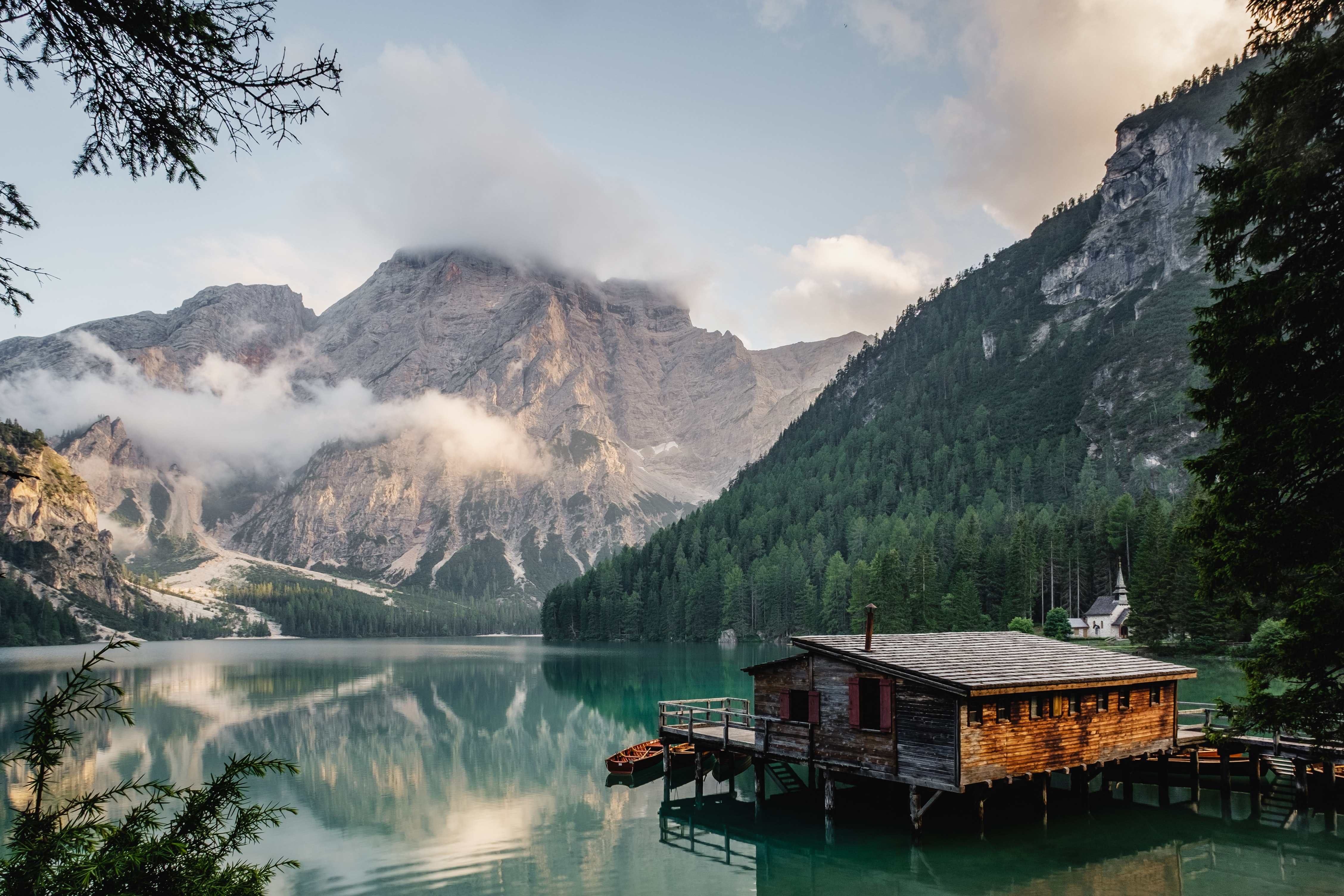A log cabin lakehouse and dock on Lago di Braies with the snow-capped mountains in the background