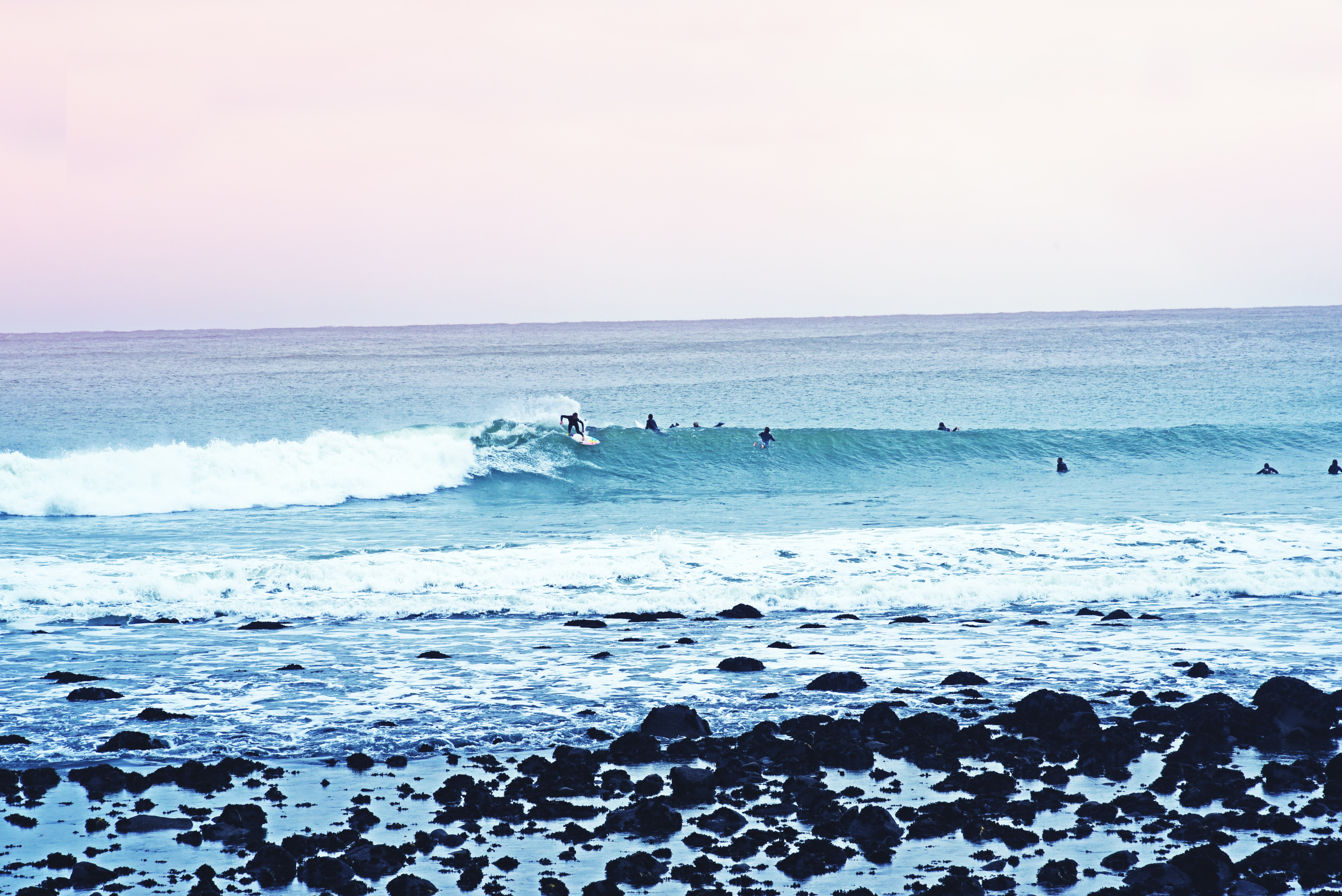 A pale shot of a surfer riding a wave with silhouettes of other people swimming in the sea nearby