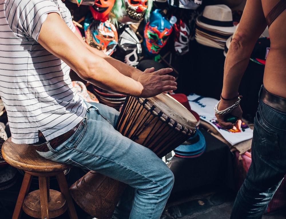 men wearing white striped shirt playing djembe