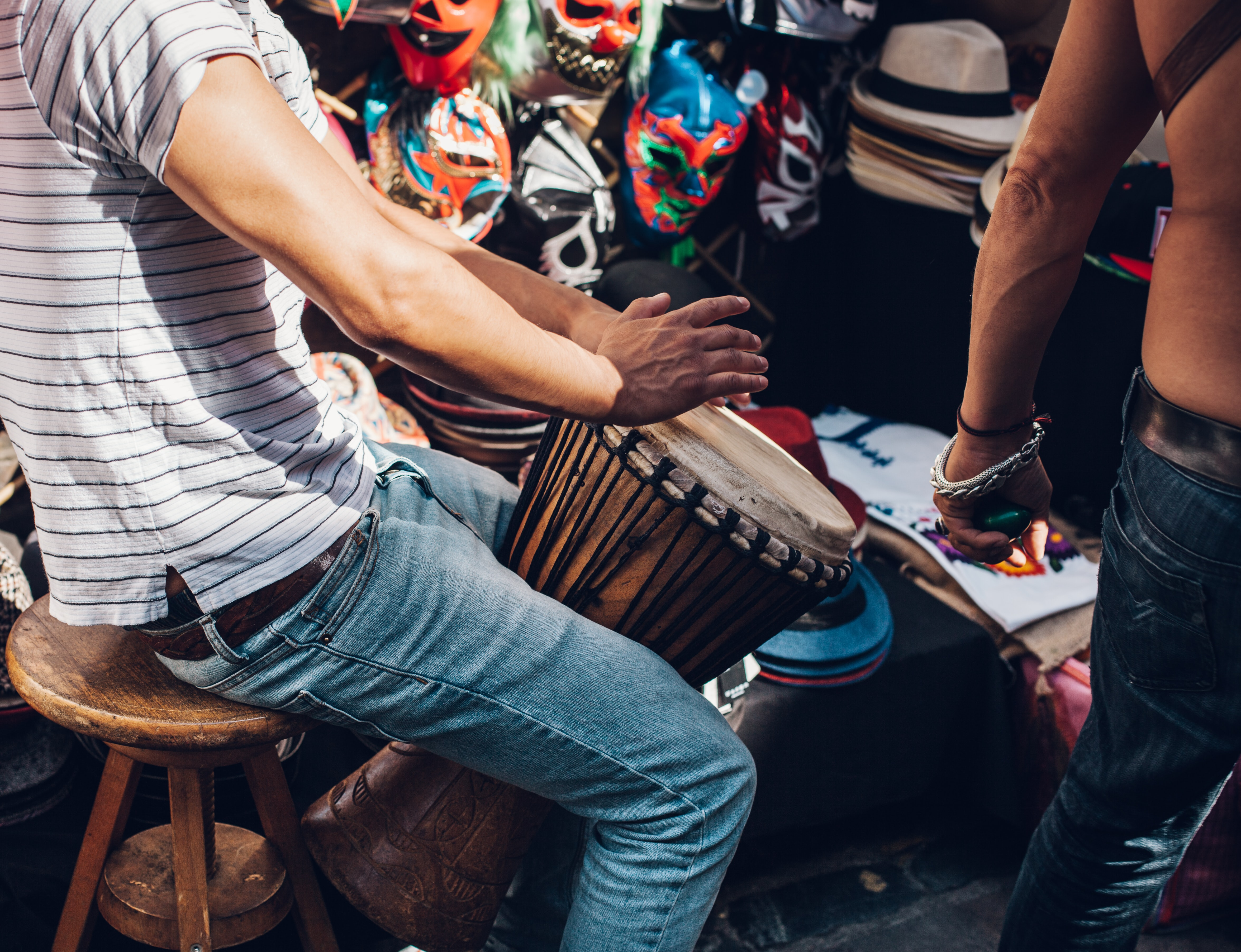 A man in jeans and t-shirt playing a tall drum on Brick Lane Market