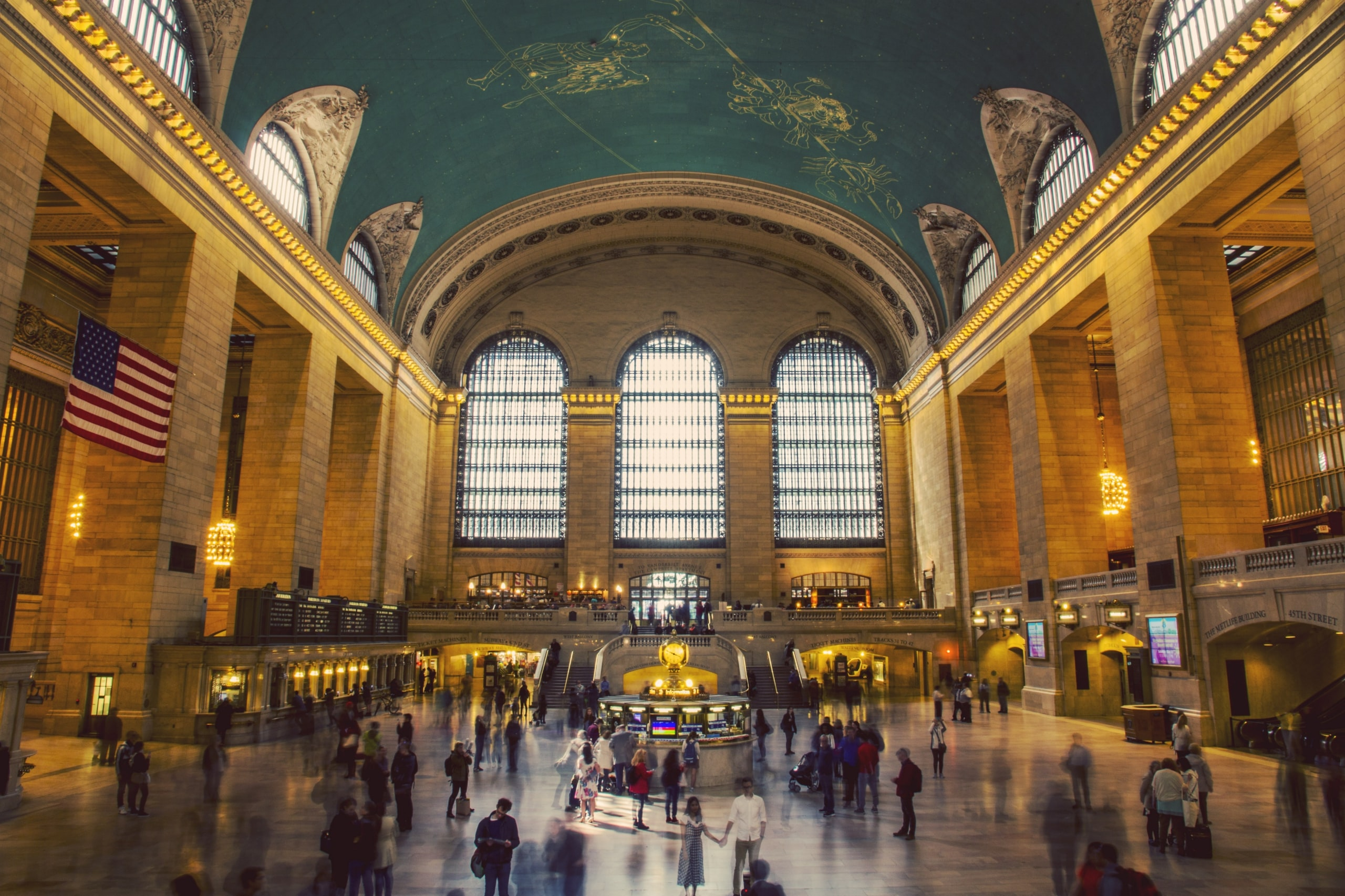 The interior of New York's Grand Central Station with an American flag on one of the walls