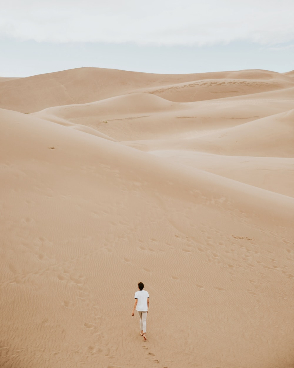person walking on sand dune