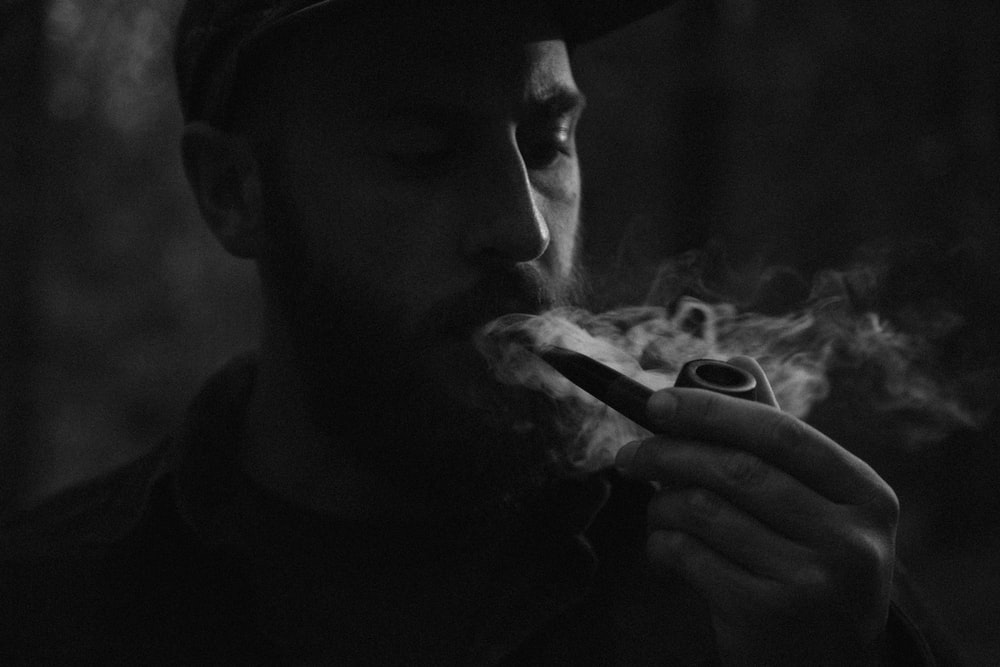 grayscale photo of man using smoking pipe