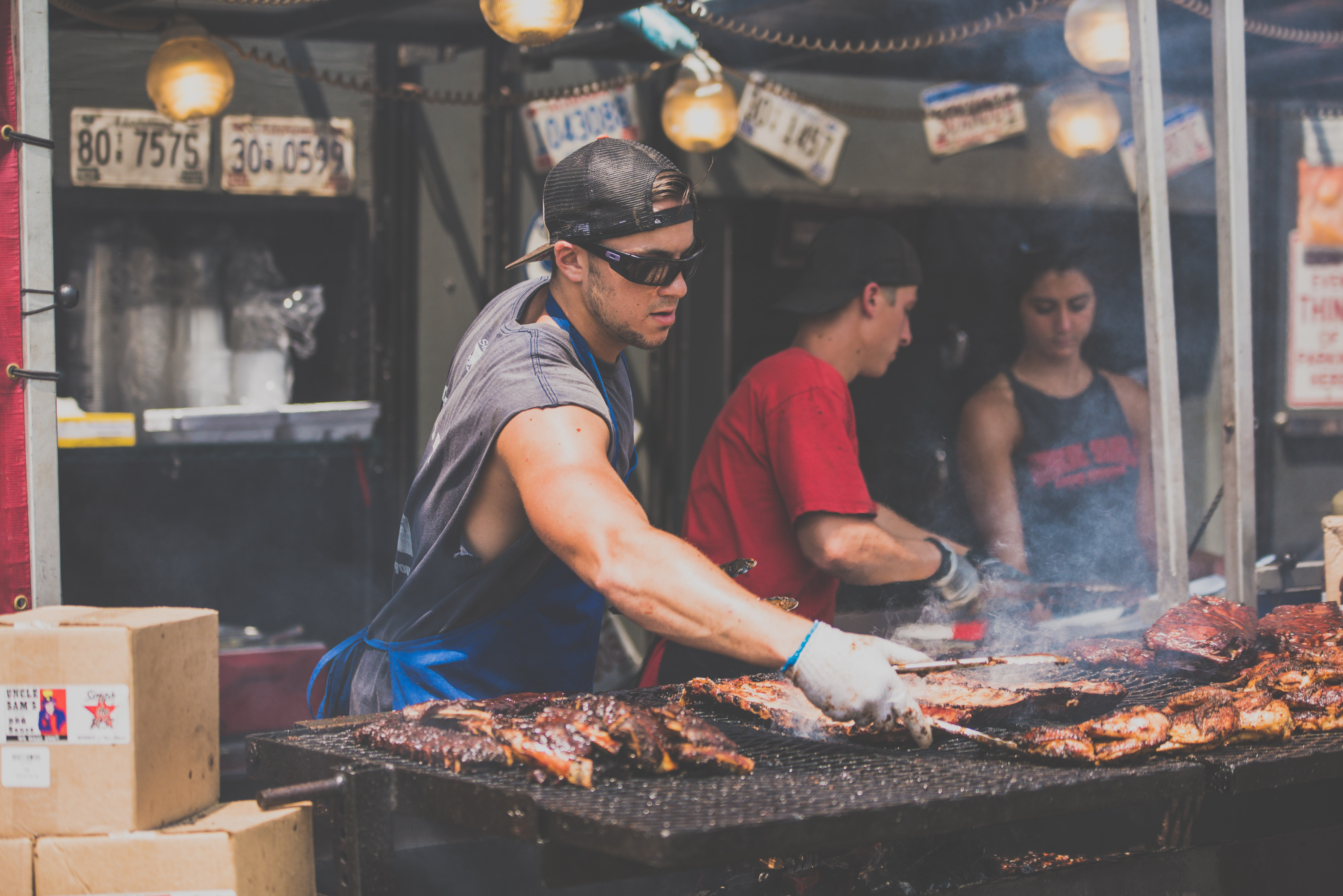 man standing infront of grill while holding tong