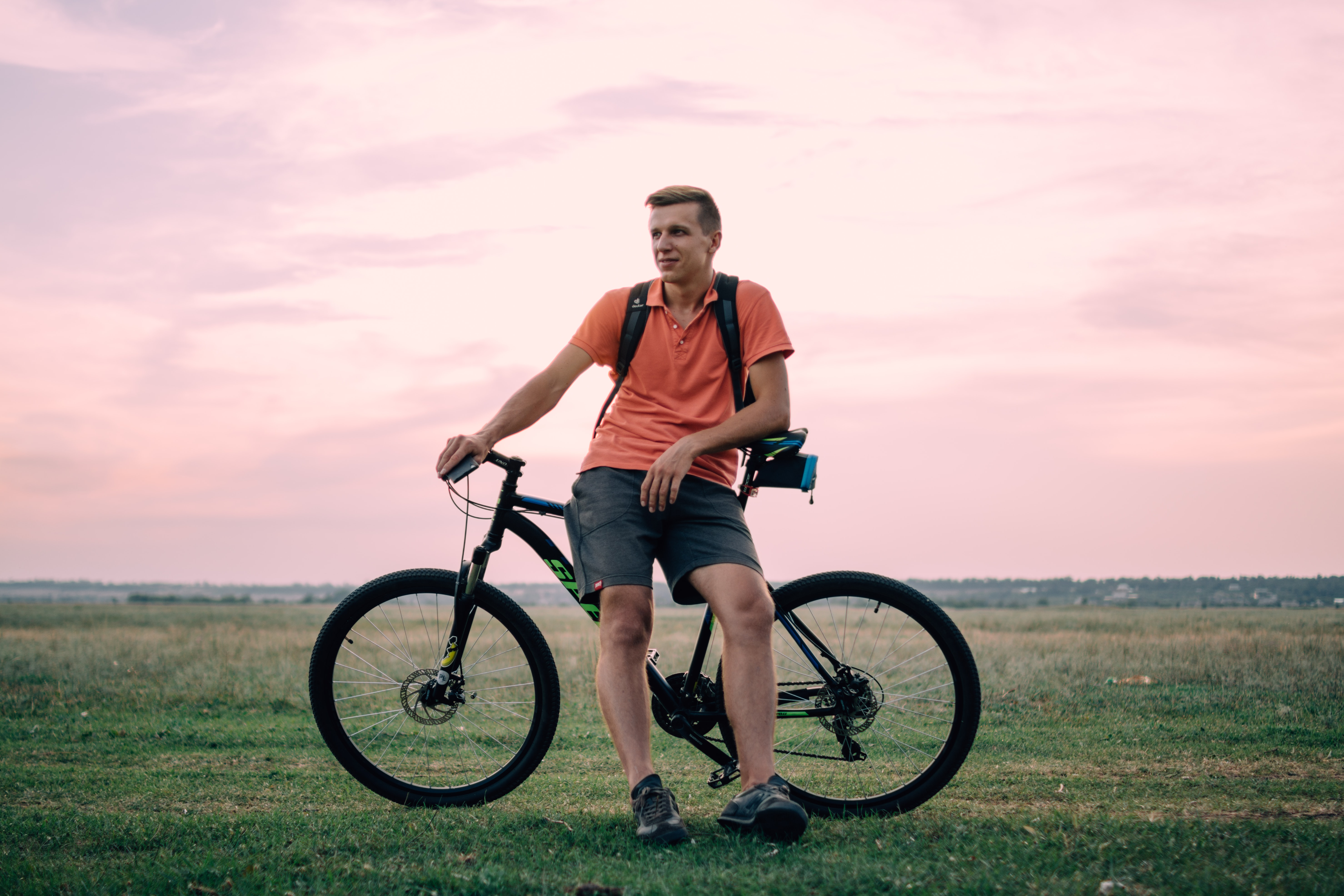 A man standing poised in a pink shirt in front of his bicycle in the country grass