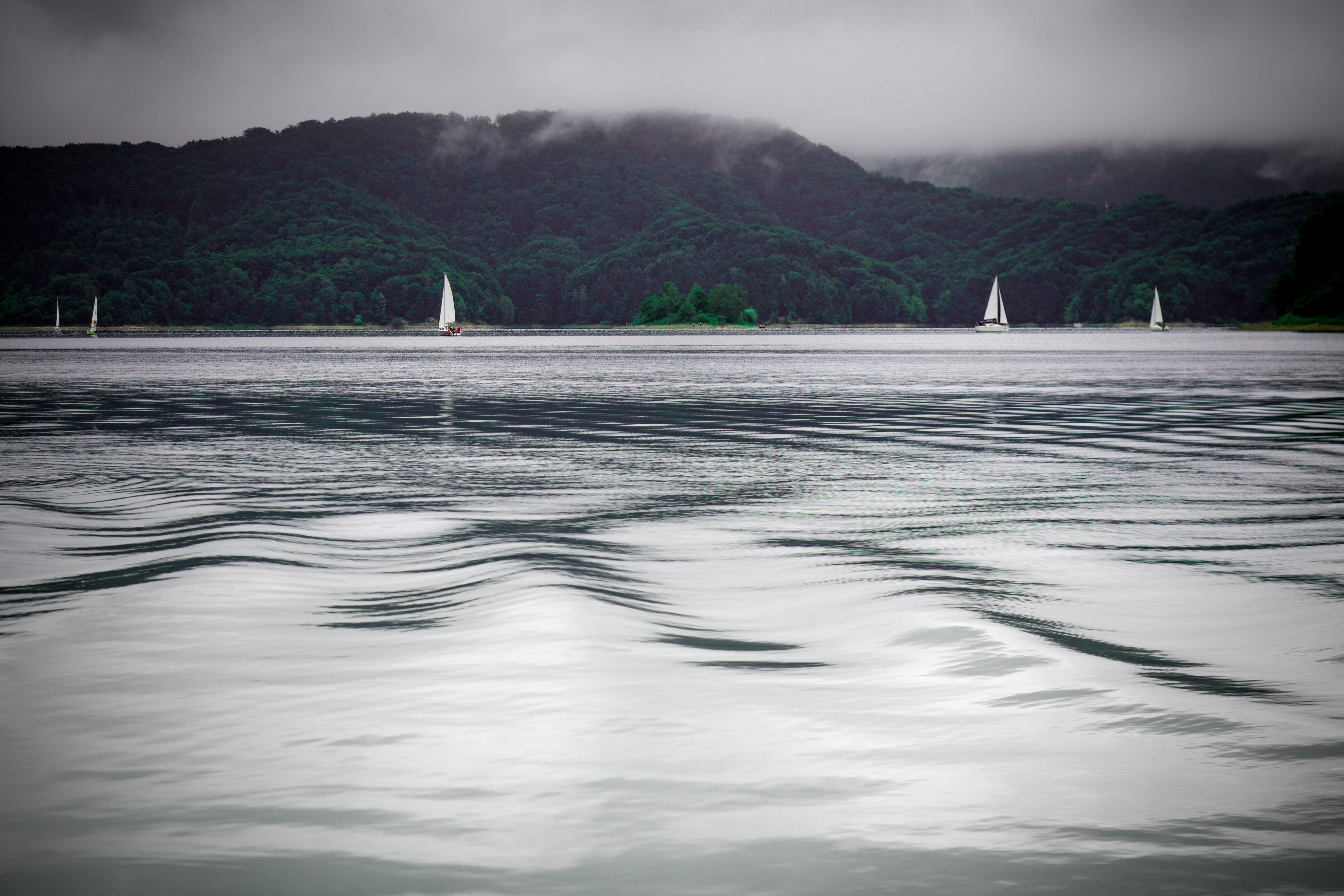 green mountains near sailboats on ocean