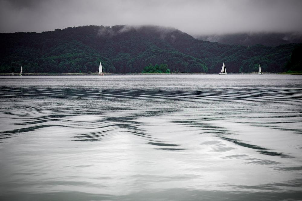 green mountains near sailboats on ocean