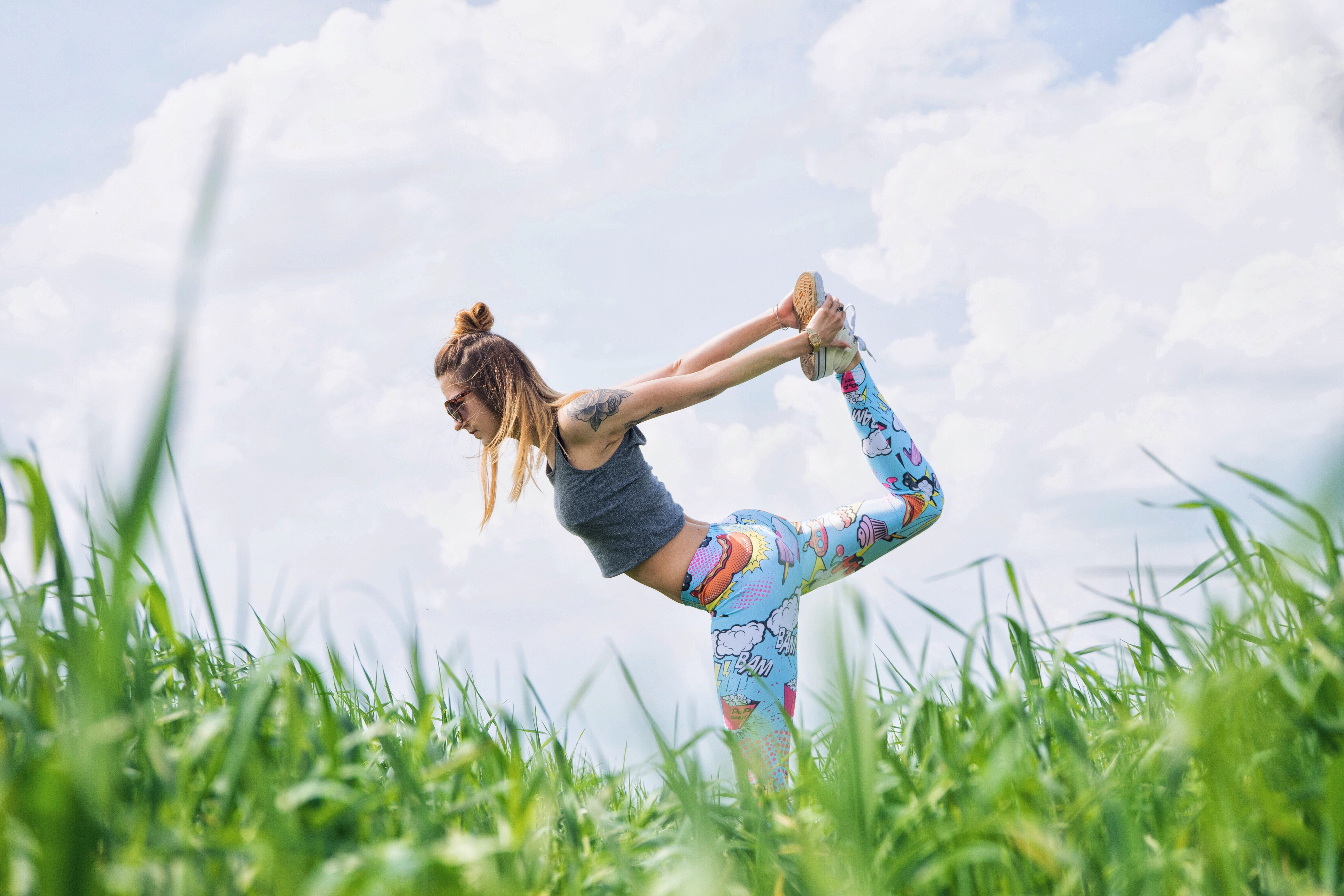 A woman wearing funky leggings doing yoga on the grass in Karczewski