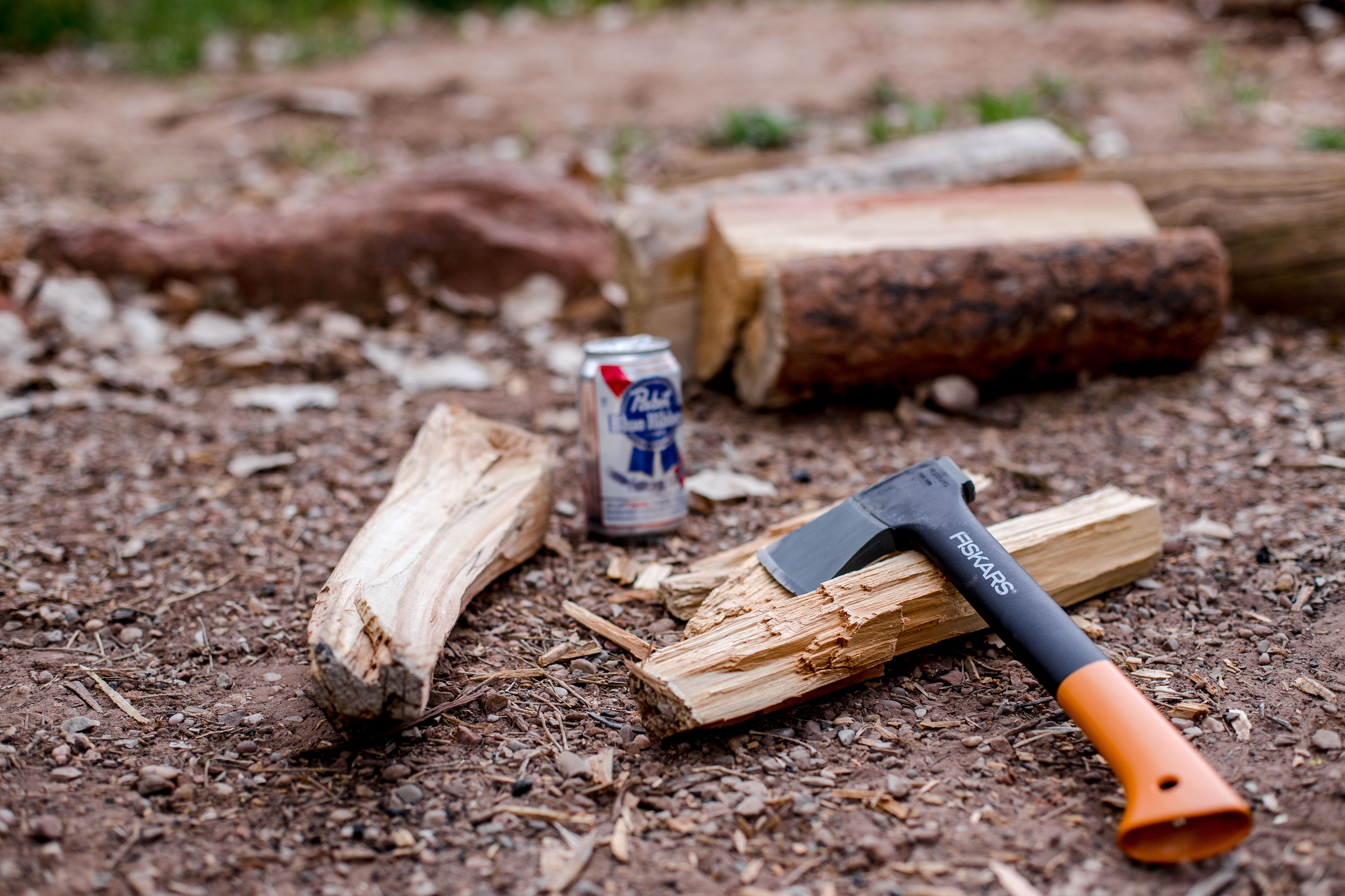 A small axe placed next to chopped wood and a beer can on the ground in Watchman Campground Site B 9