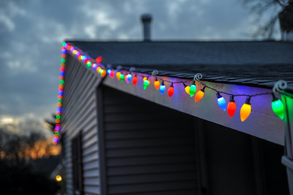 selective focus photography of string lights on roof top edge