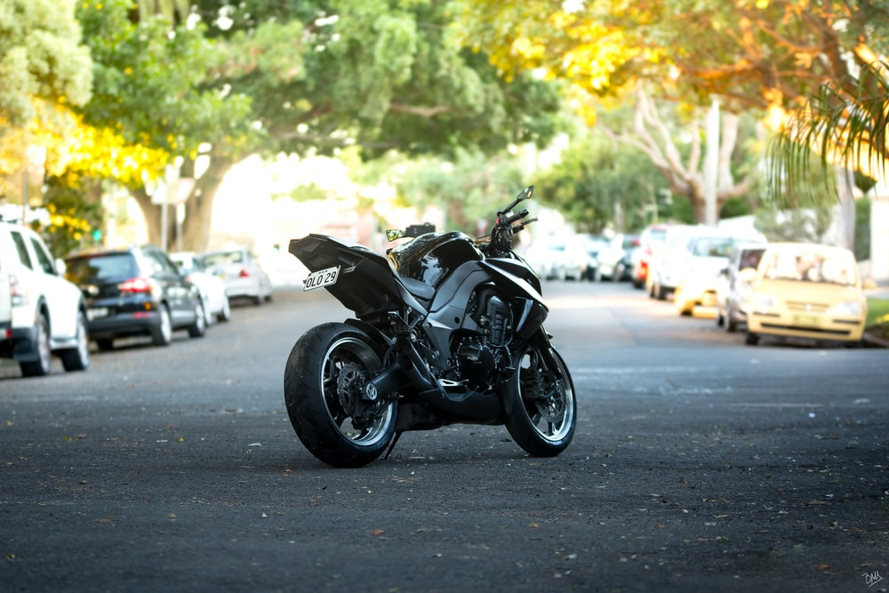 black sports motorcycle in middle of street