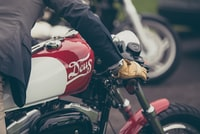 person riding red and gray motorcycle