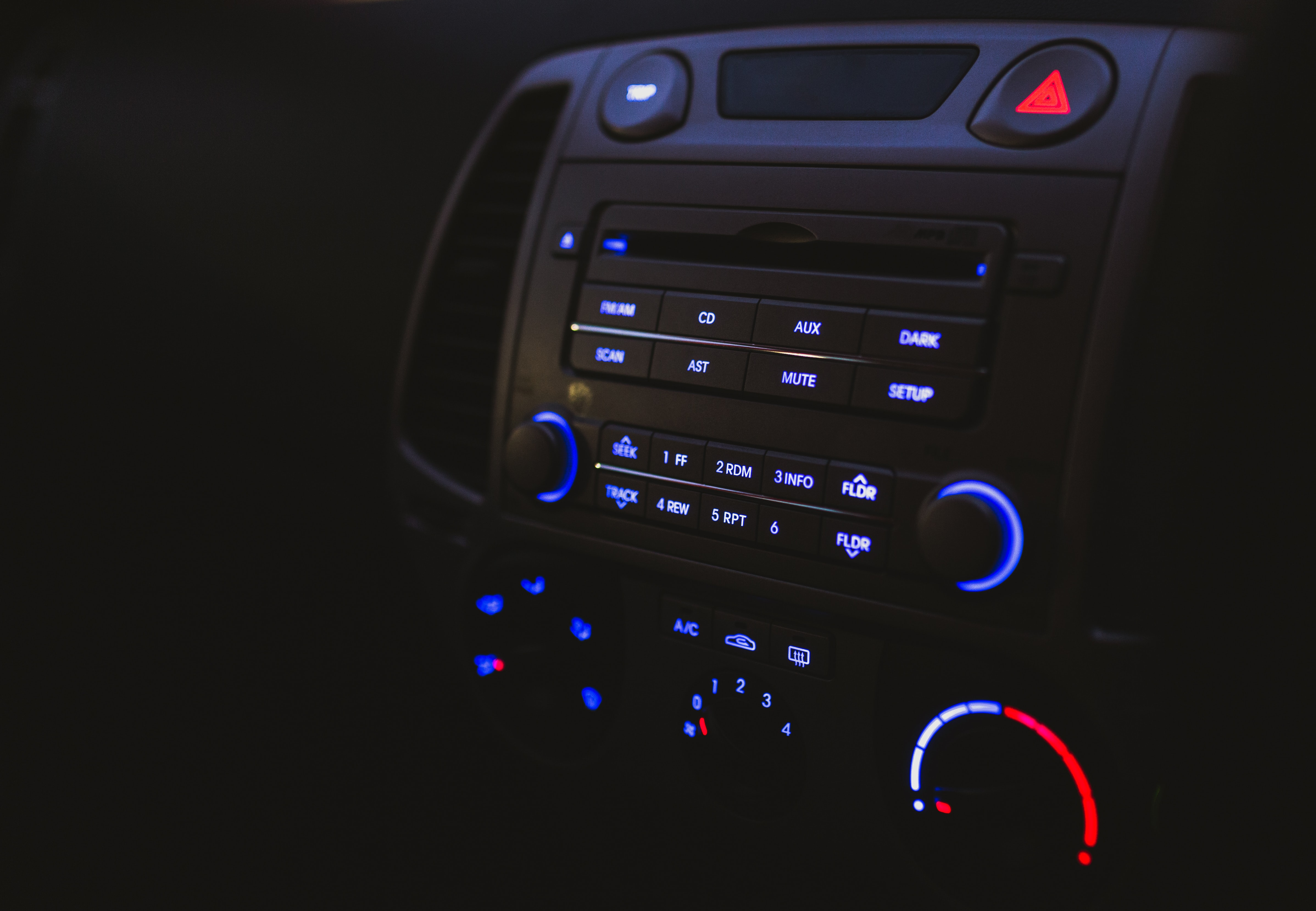 A dim shot of a car radio with gauges and buttons lighting up in red and blue