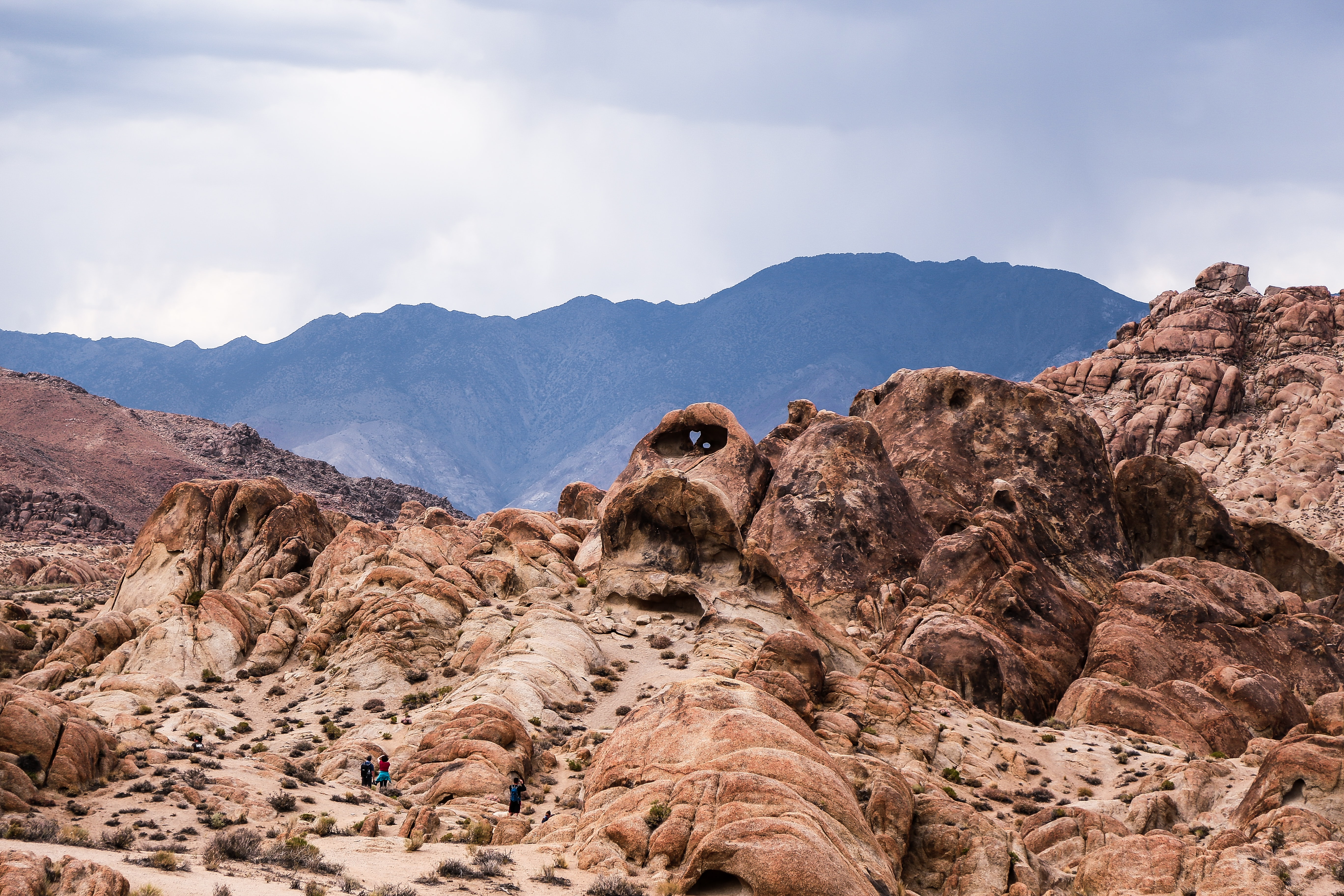 brown rock formation near mountain under cloudy sky