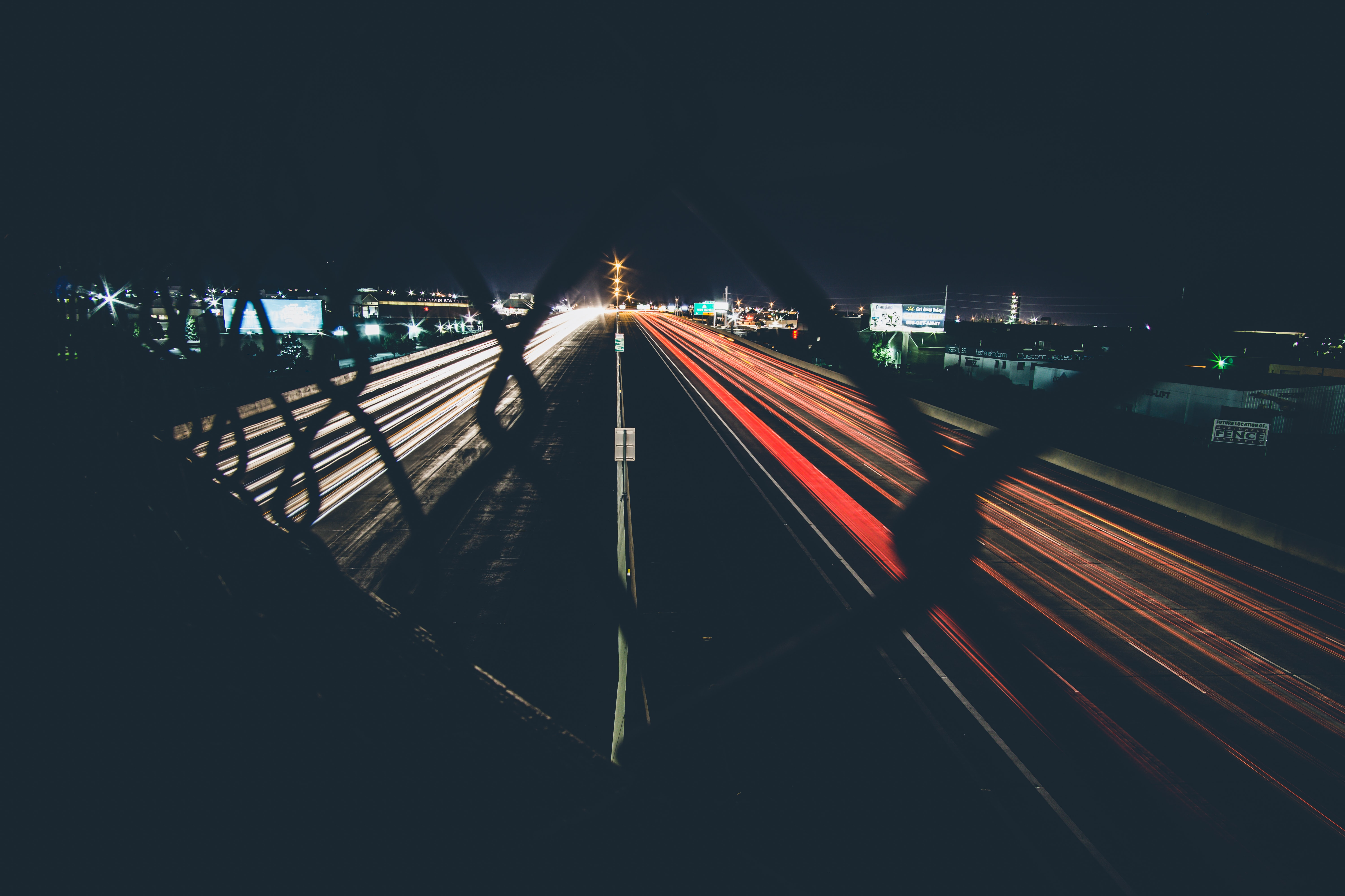 A night-time shot of car trails on a dual highway from behind a fence