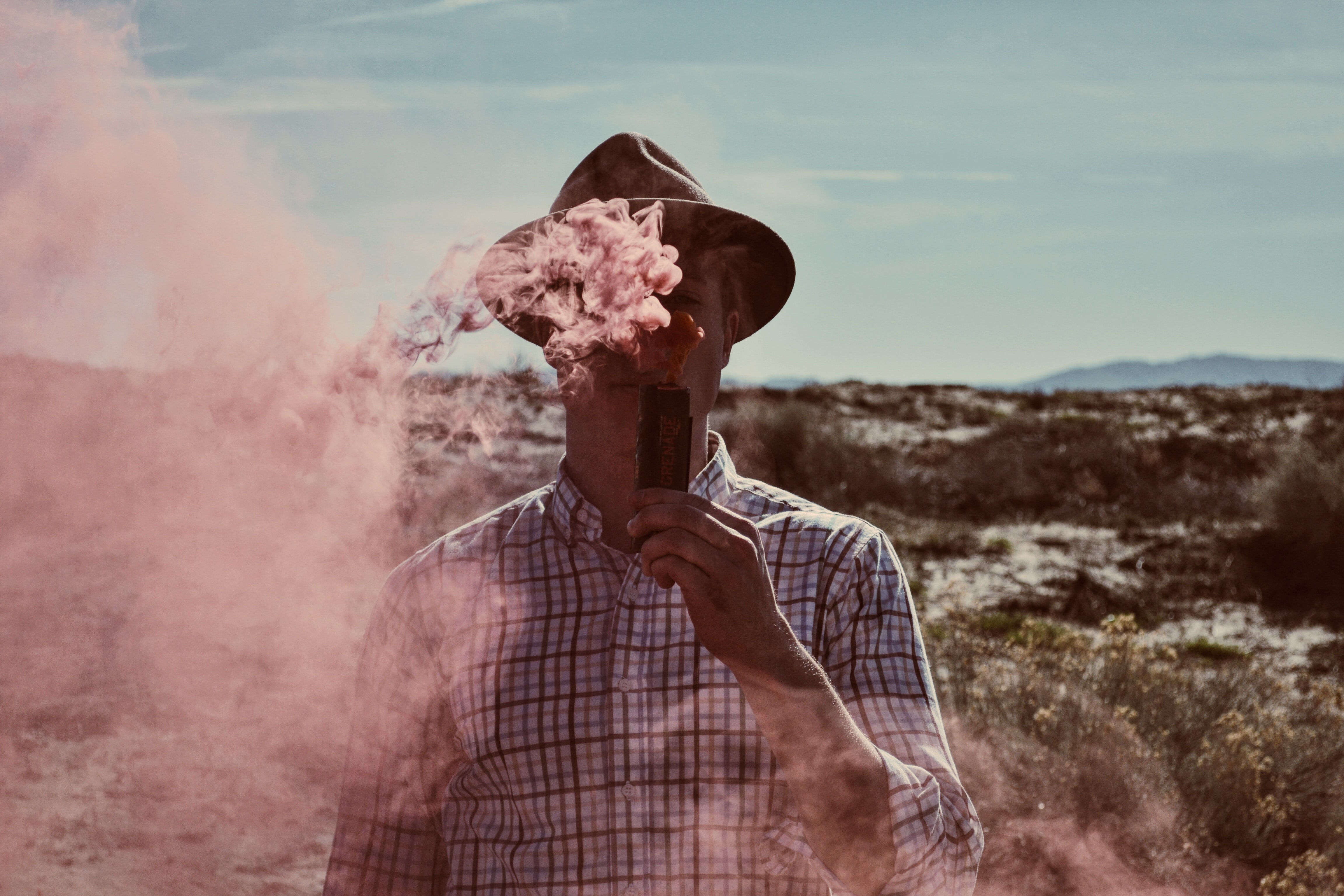 Artistic portrait of a man burning red smoke in the desert