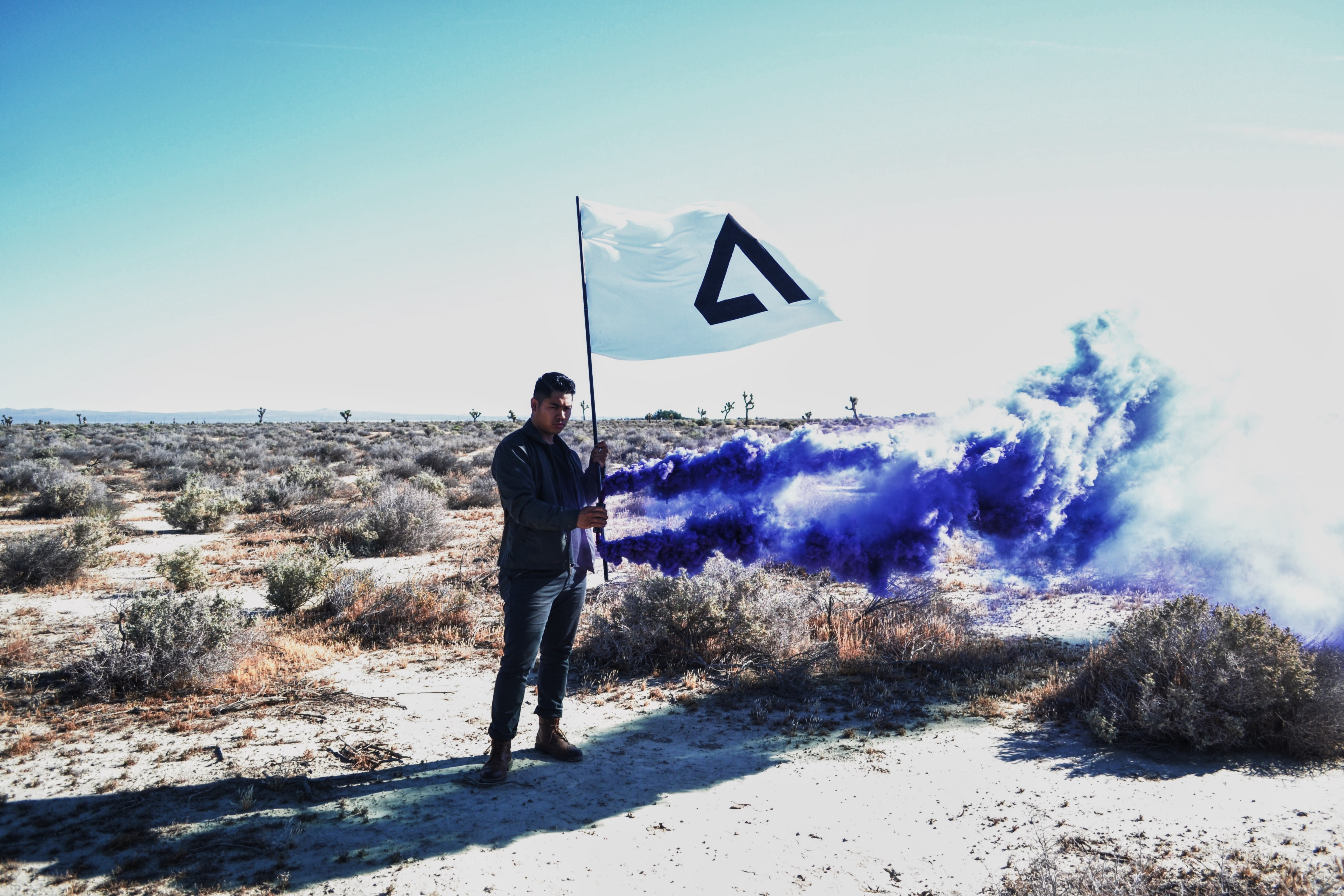 A man holding a flag with smoke surround him.
