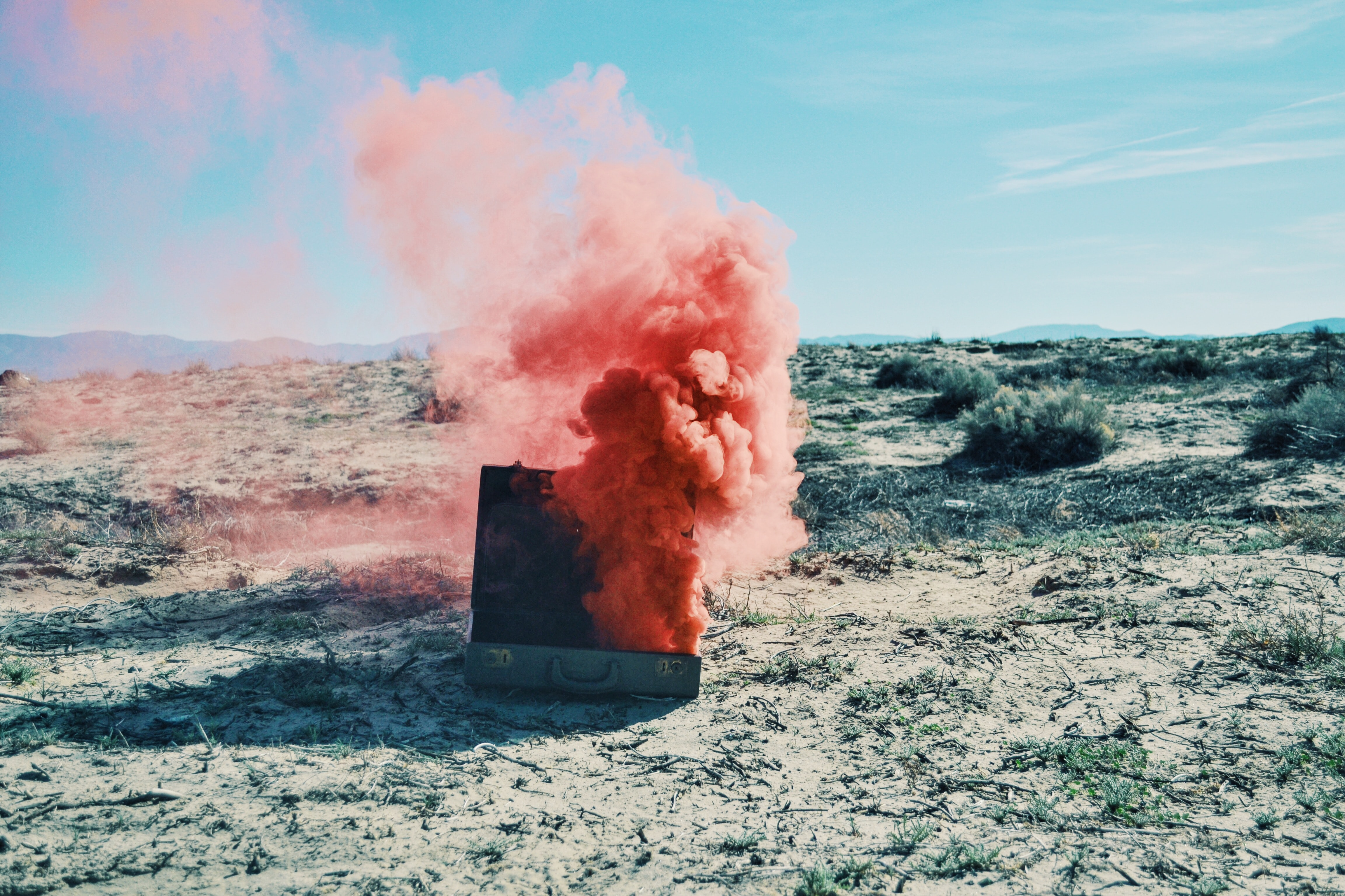 Red smoke billows from a suitcase in a sandy desert