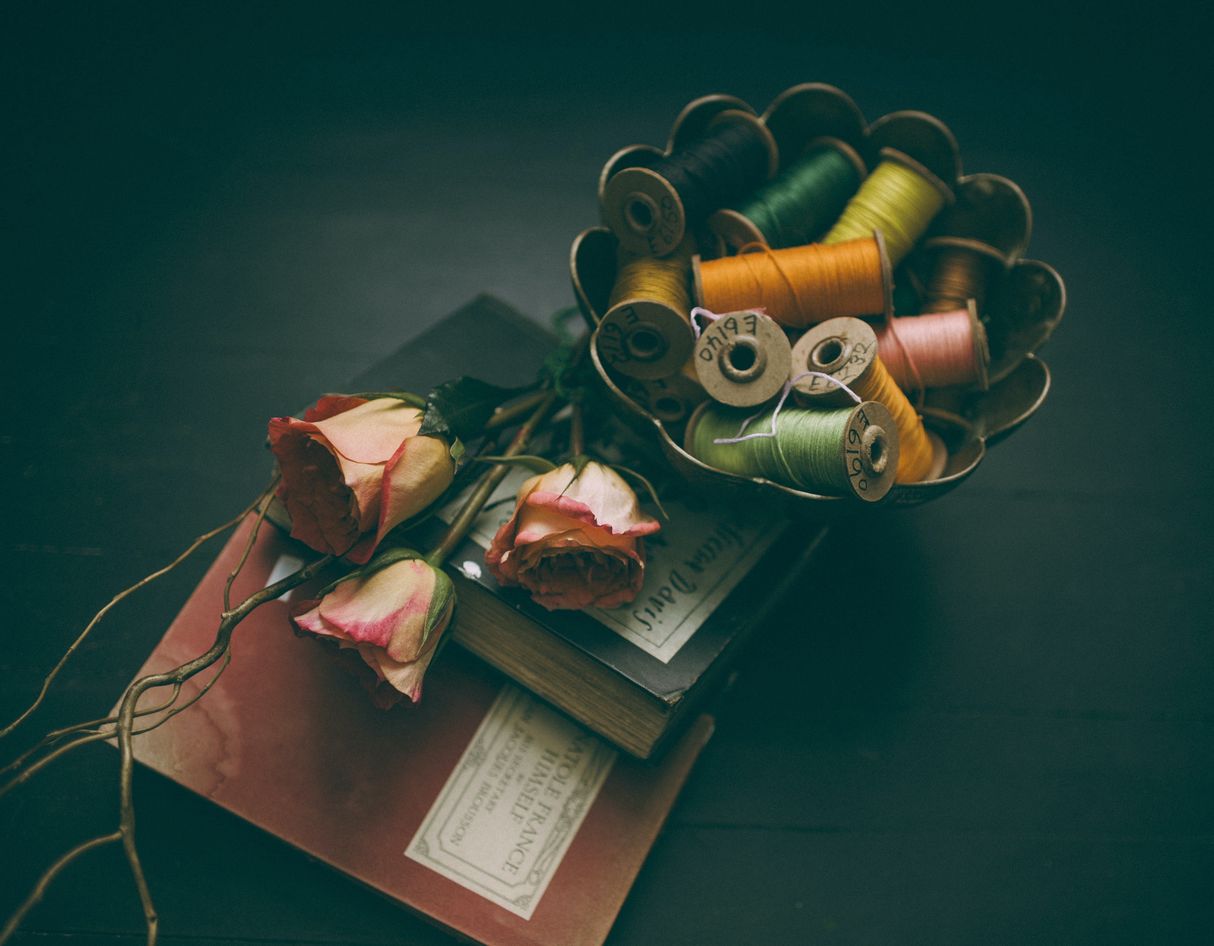 Colorful spools of thread in a bowl next to two books and three pink roses