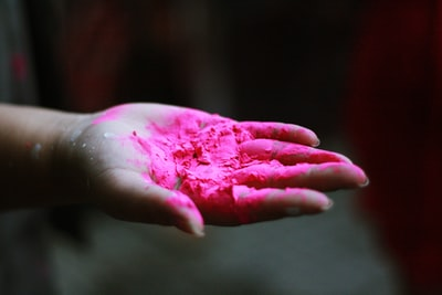 pink powder in right human palm create zoom background