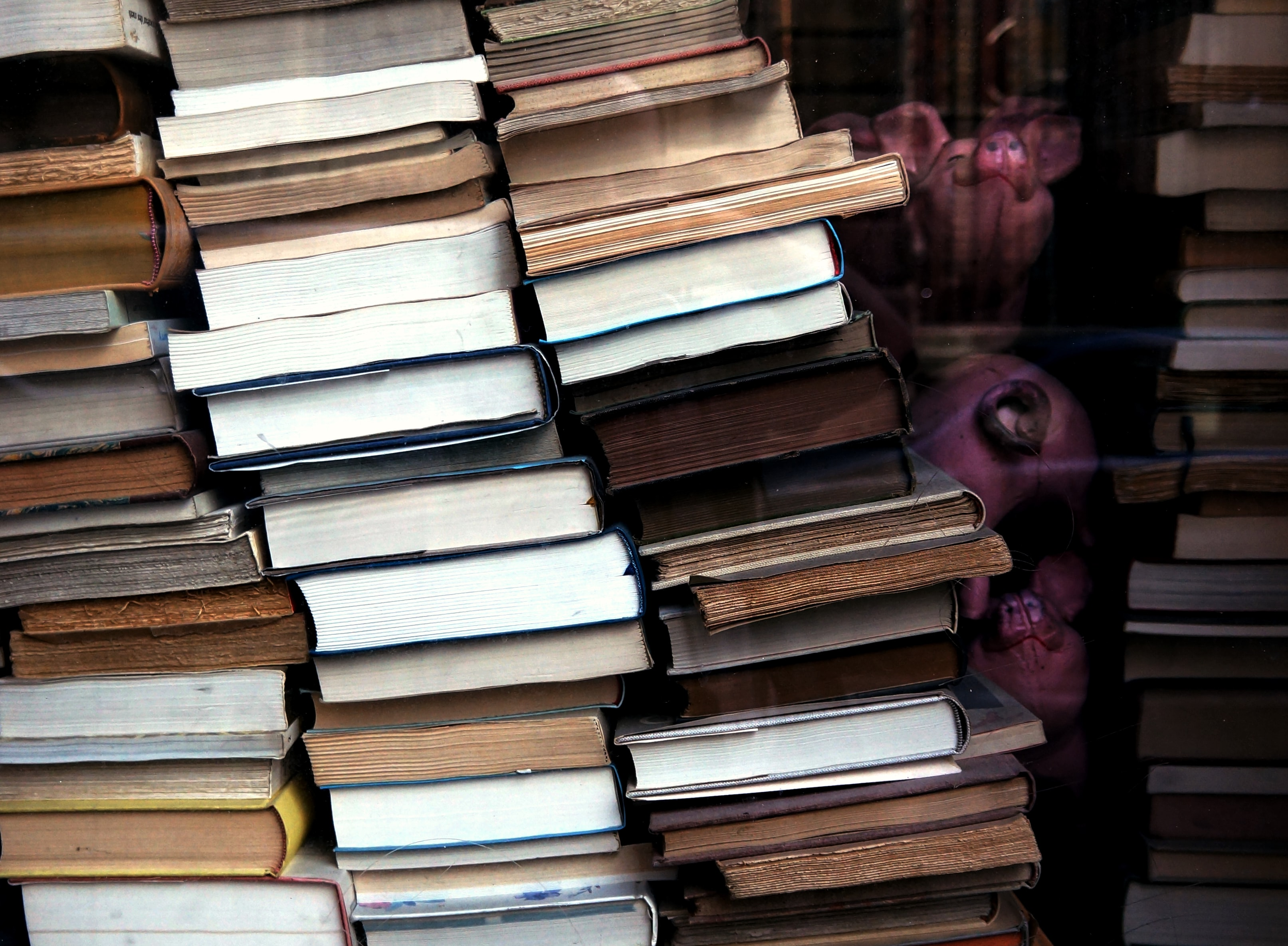 Stacks of antique second-hand hardback books piled up inside of a store window.